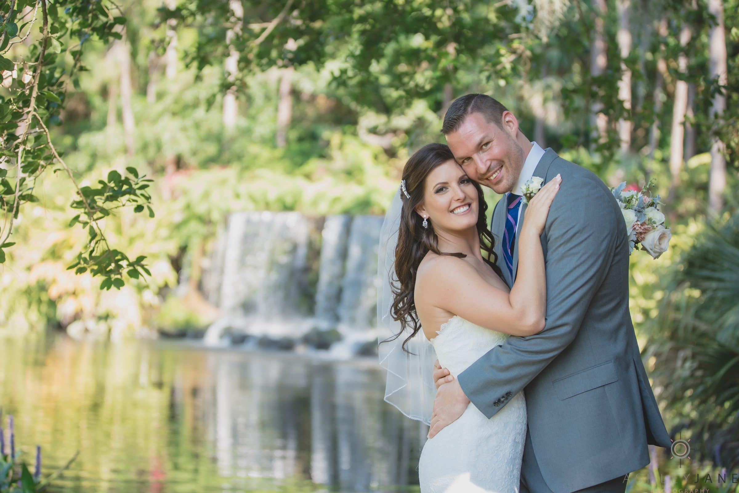 Bride and groom next to golf course waterfall feature