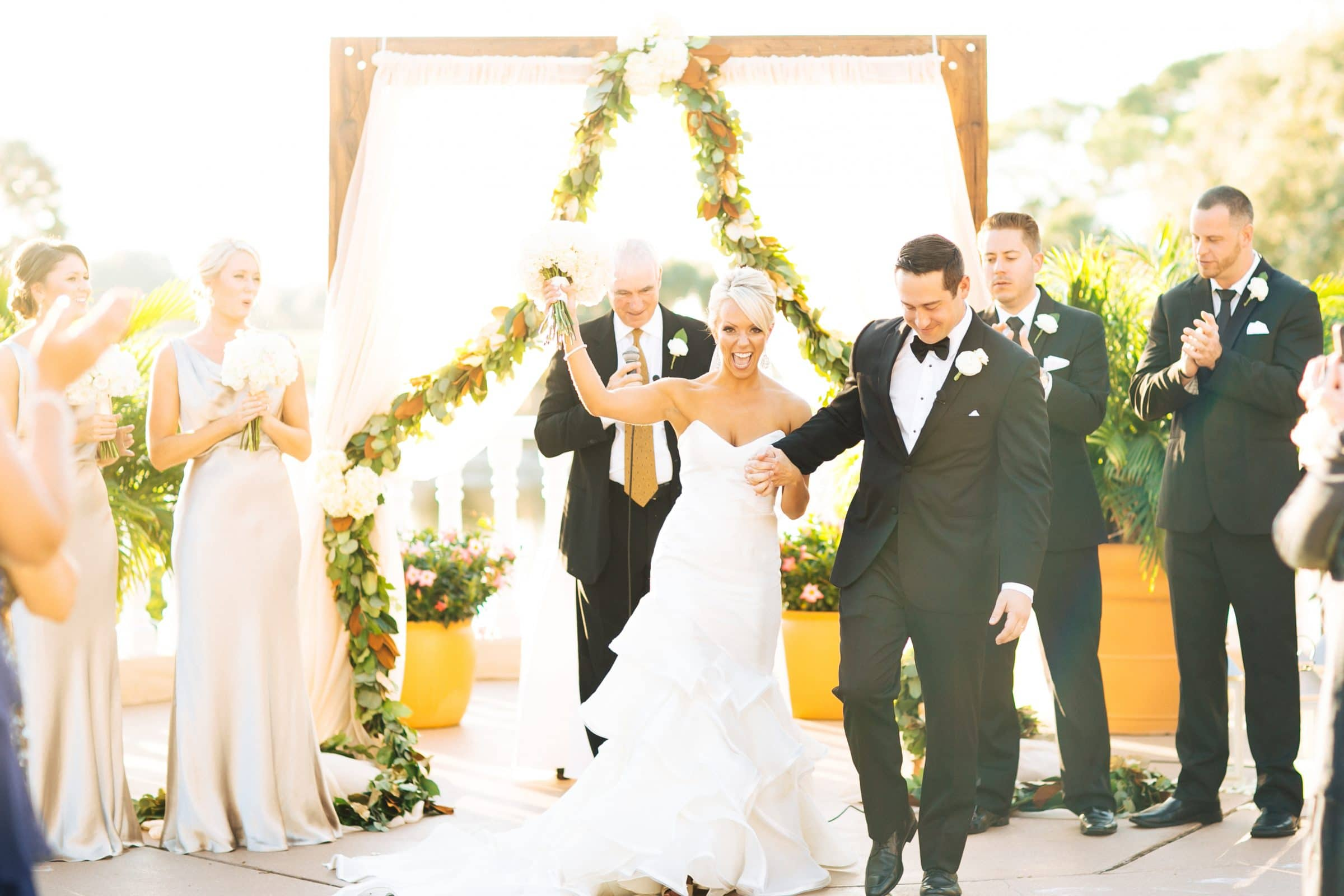 Bride cheering next to smiling groom after wedding ceremony