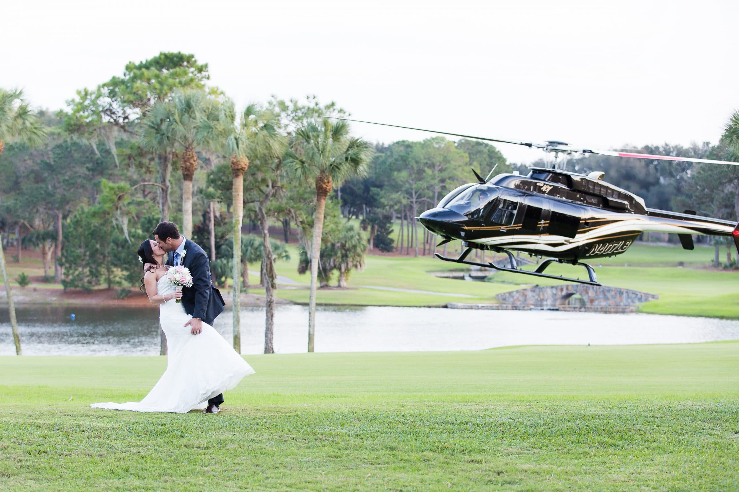 Bride and groom kissing while helicopter lands on golf course at Mission Inn
