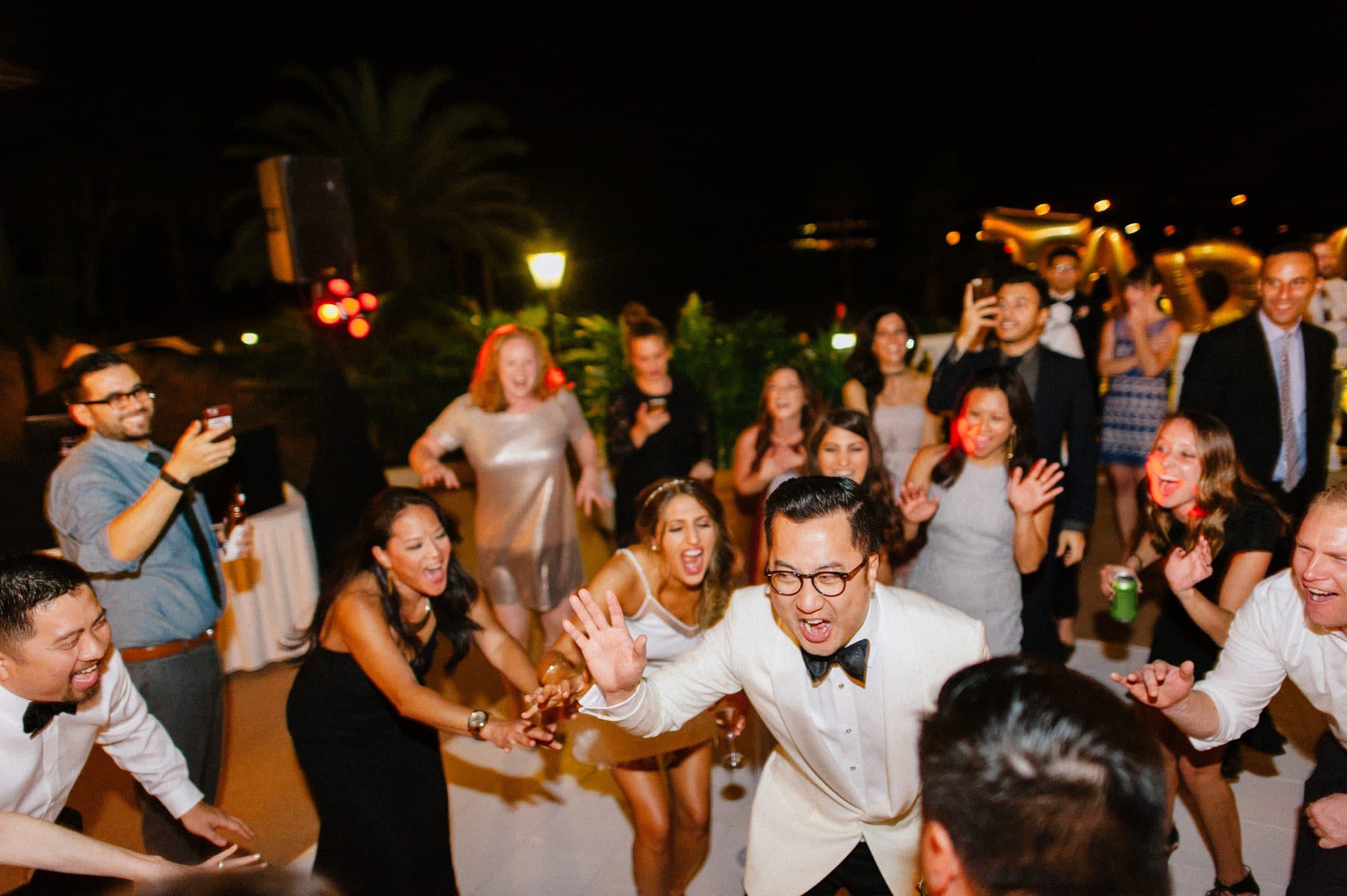 Groom partying with guests on outdoor dance floor