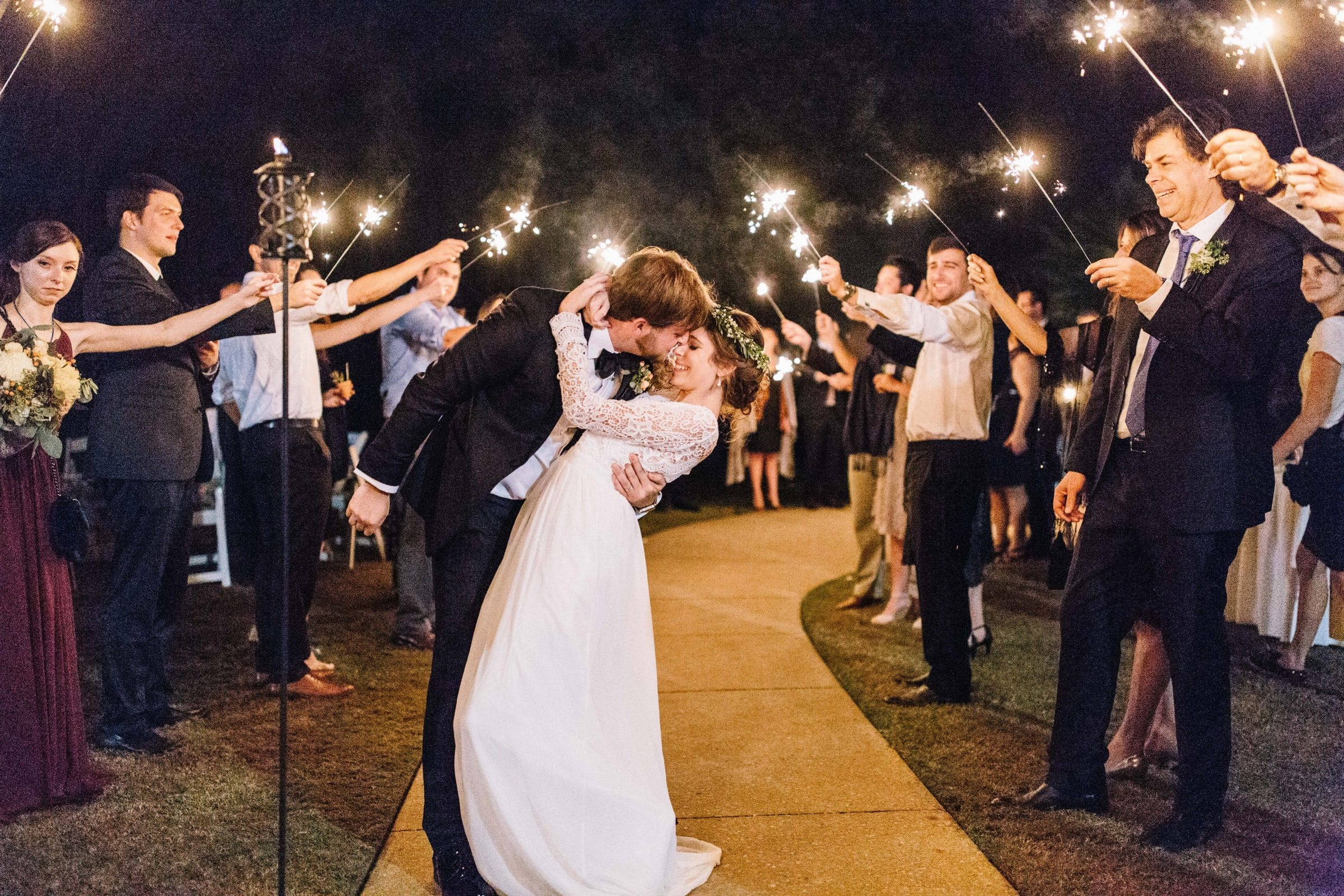 Groom dipping boho chic bride during sparkler sendoff