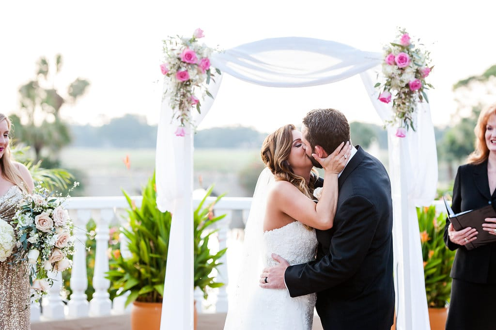 First kiss in front of romantic draped arch