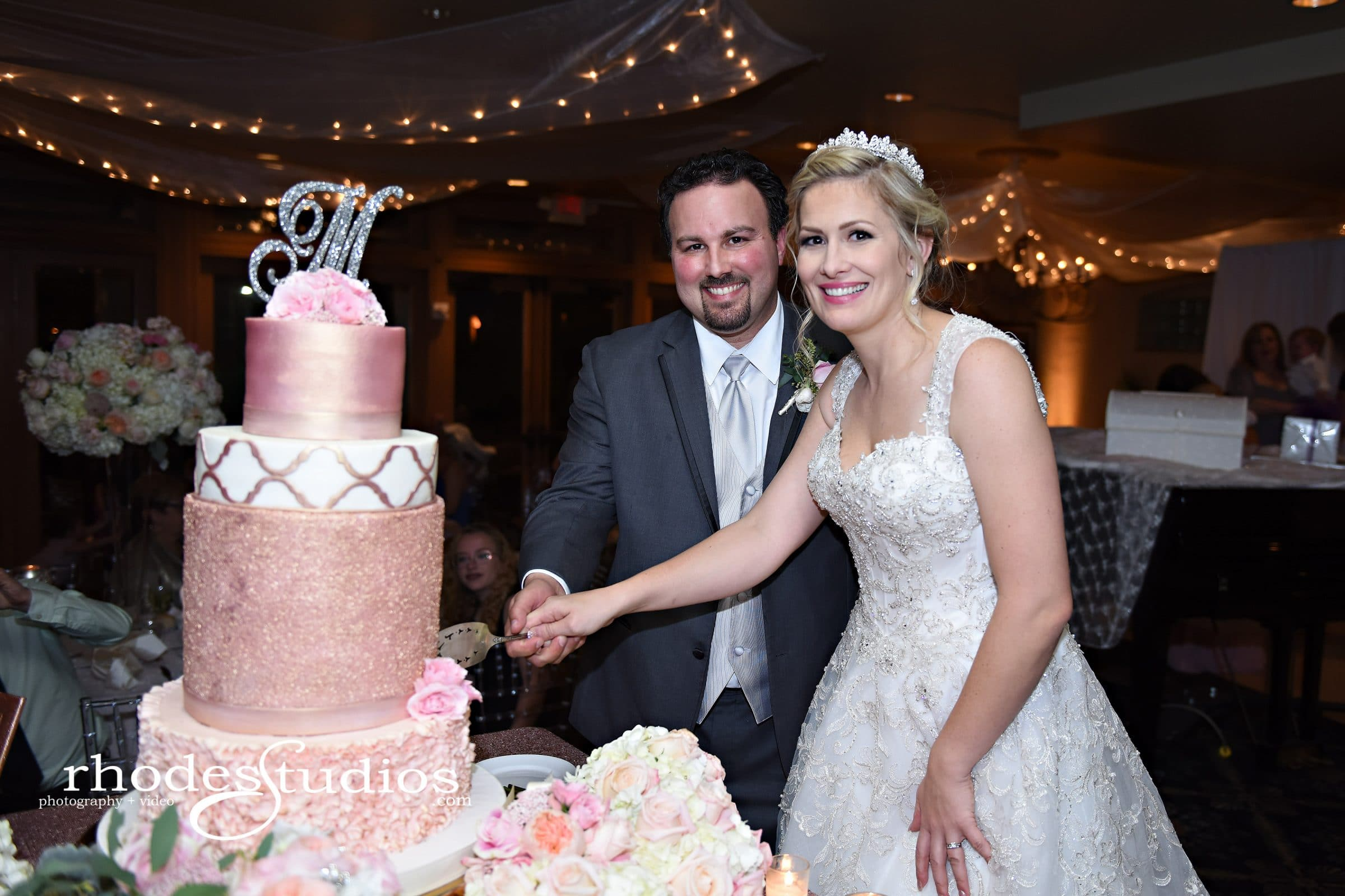Bride and groom smiling while cutting large pink wedding cake