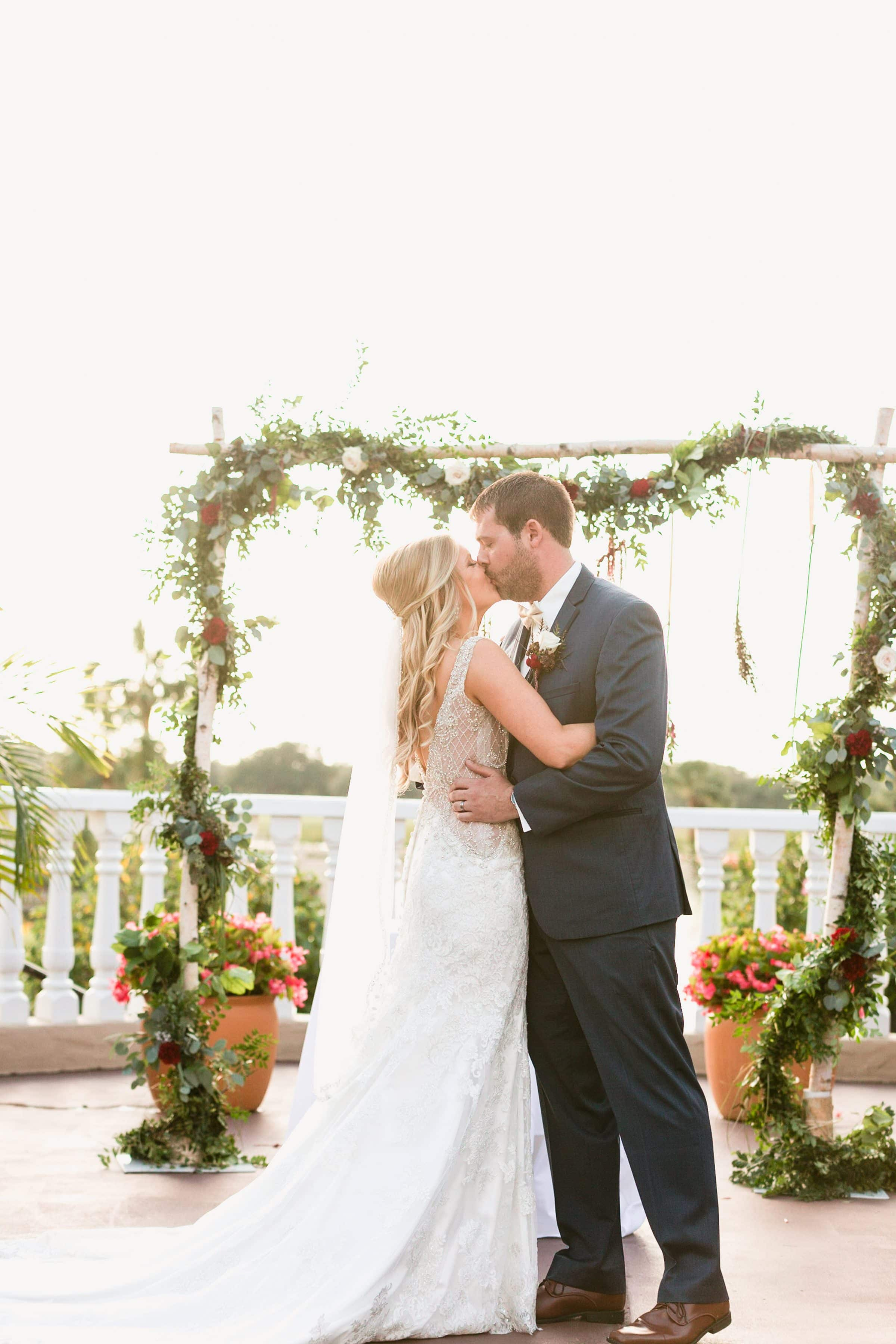 First kiss in front of rustic wooden trellis