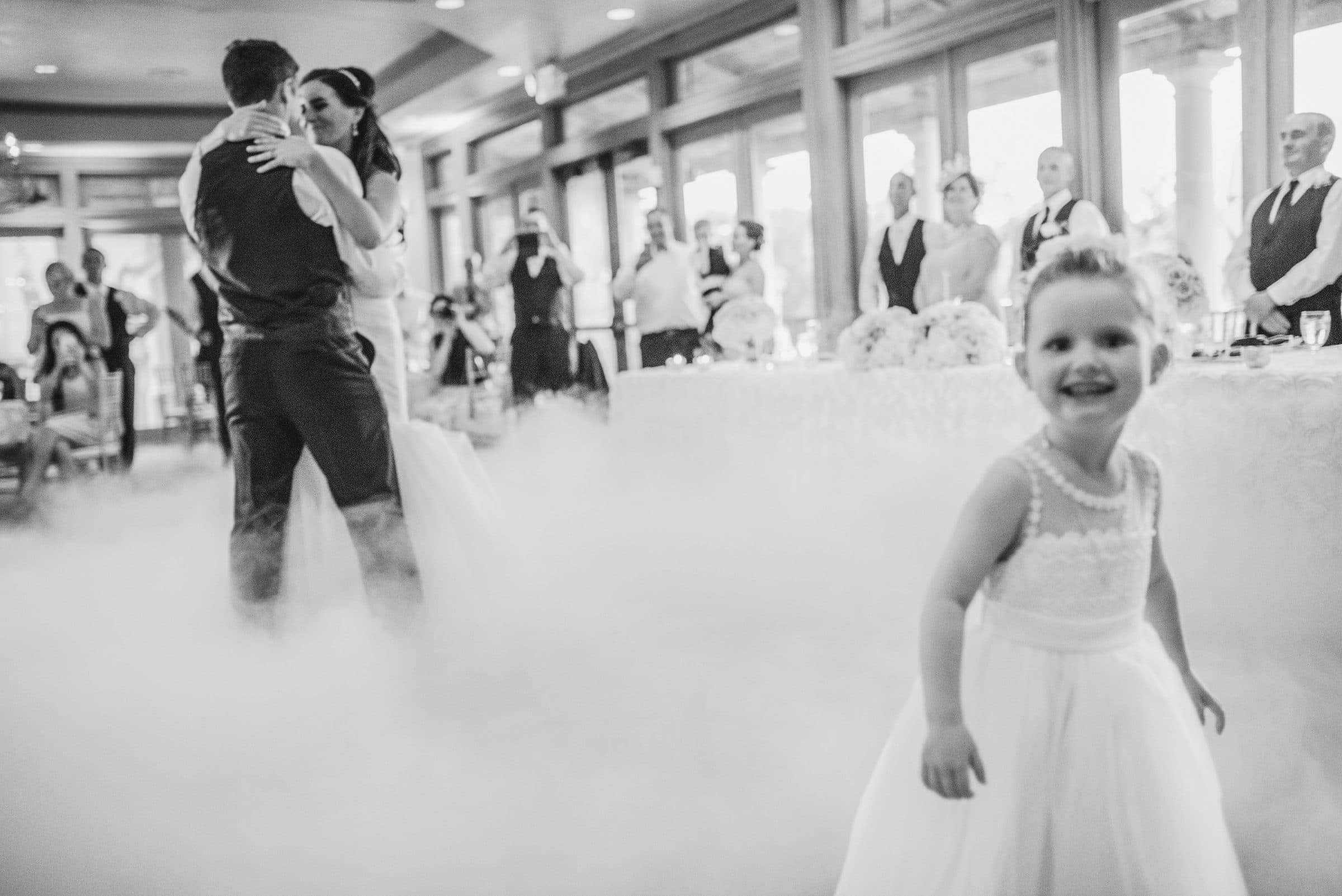 Bride and groom dance on a cloud with cute flowergirl in foreground