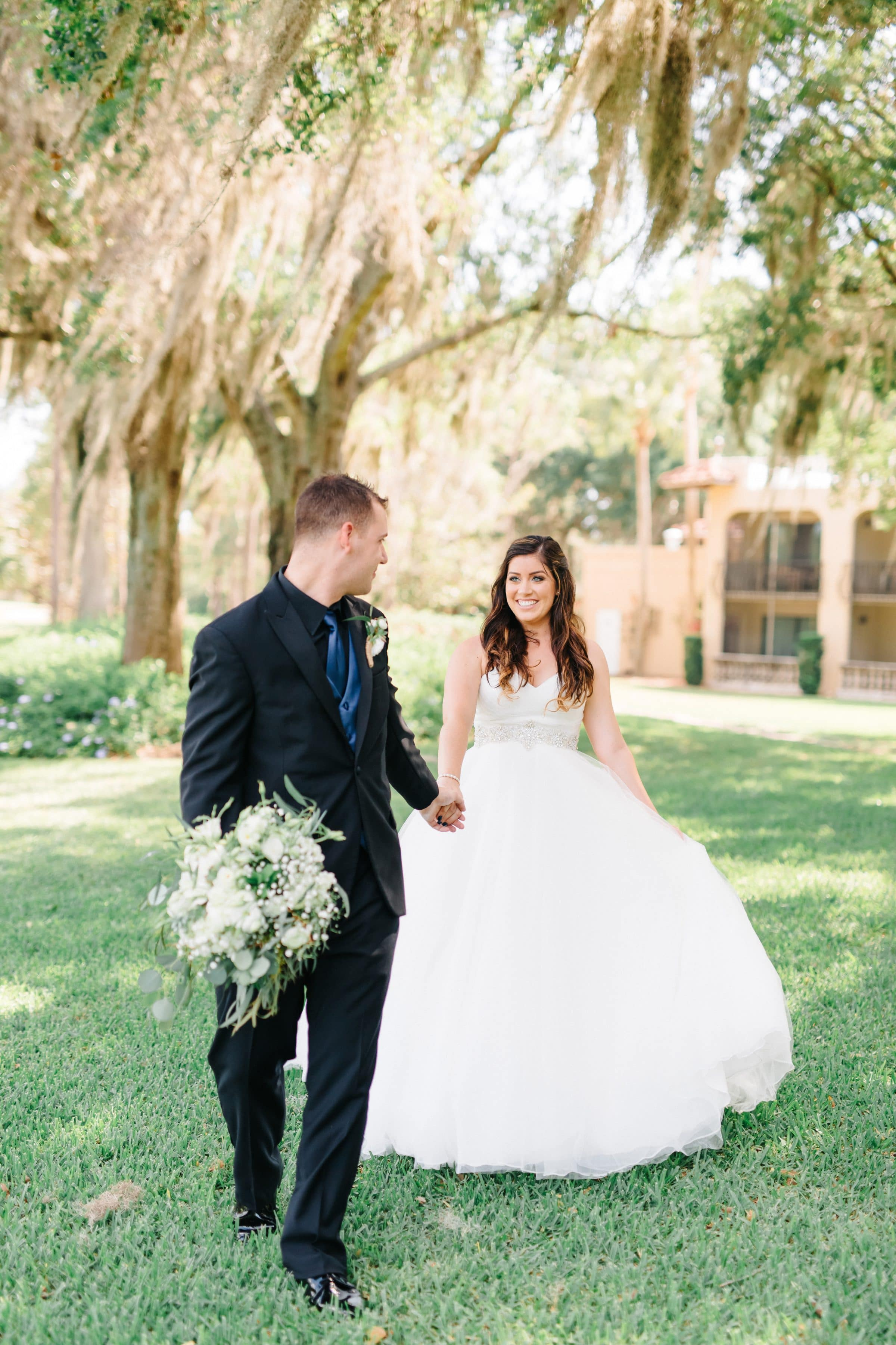 Groom holding bride's bouquet and leading her through lush field
