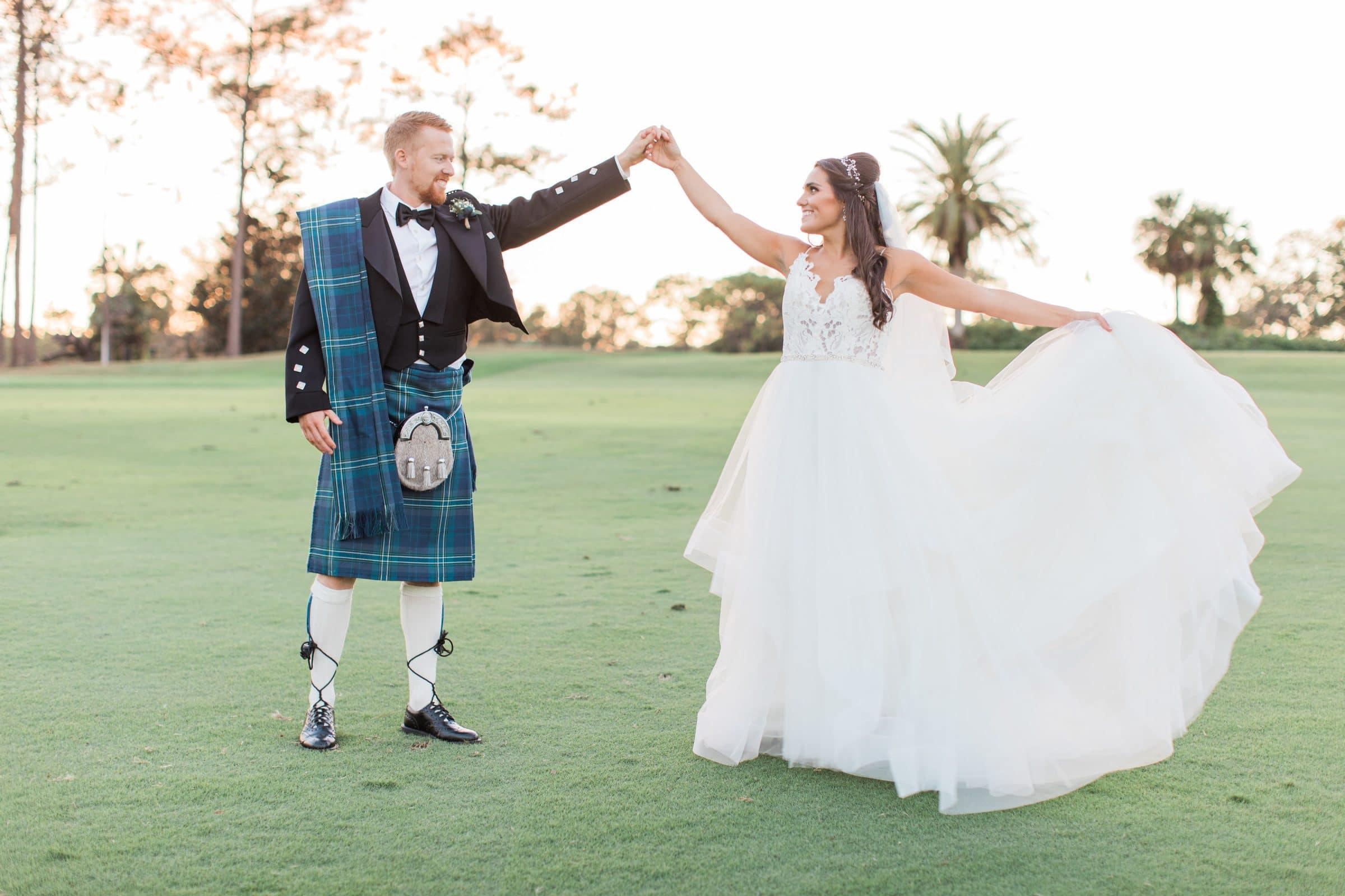 Scottish groom holding bride's upraised hand