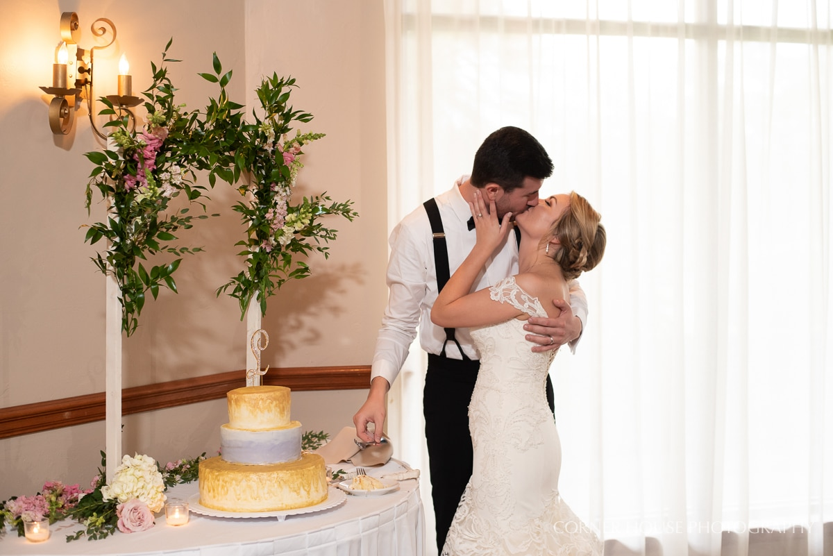 Bride and groom kiss next to yellow and blue wedding cake