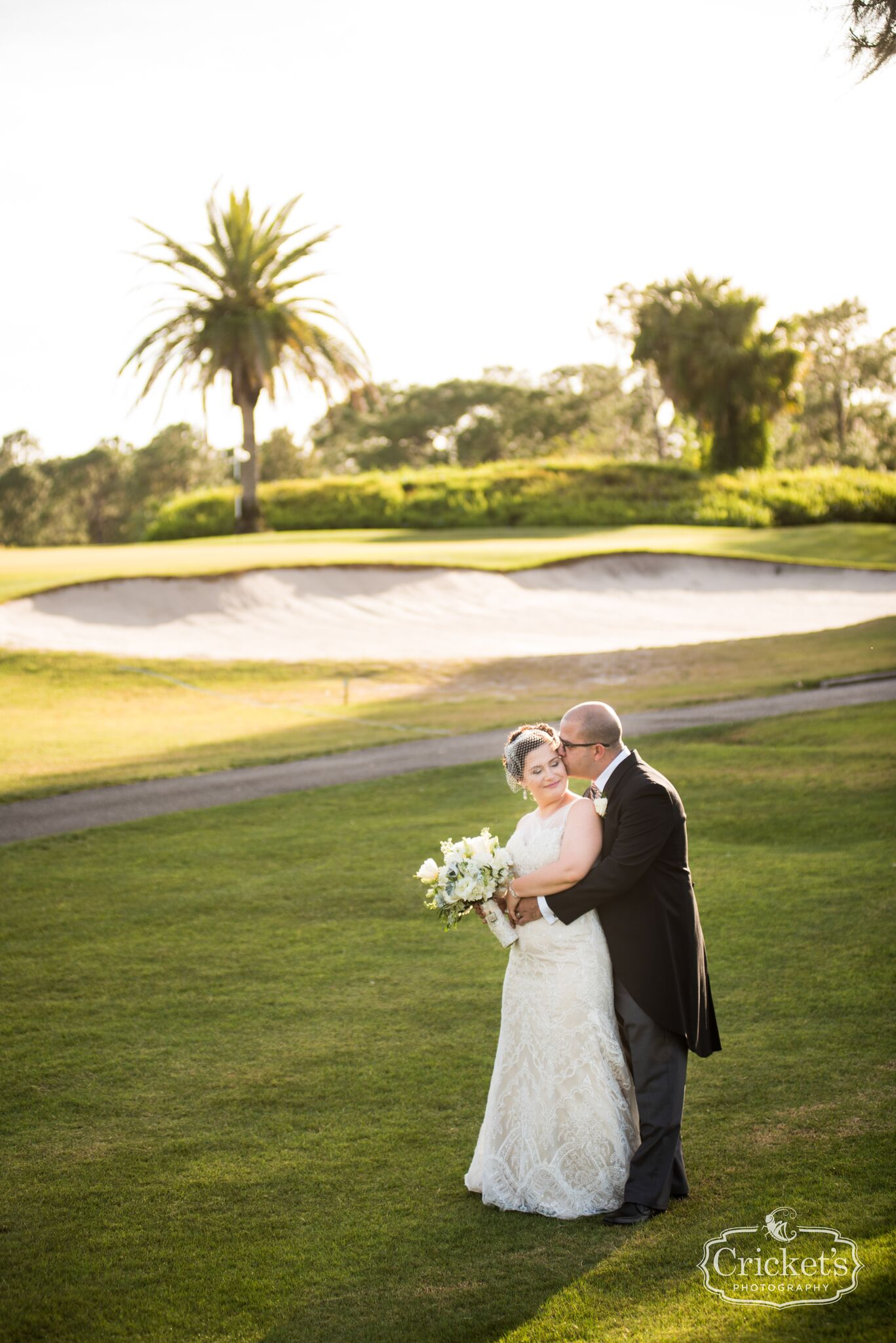 Groom embracing bride from behind on Mission Inn golf course