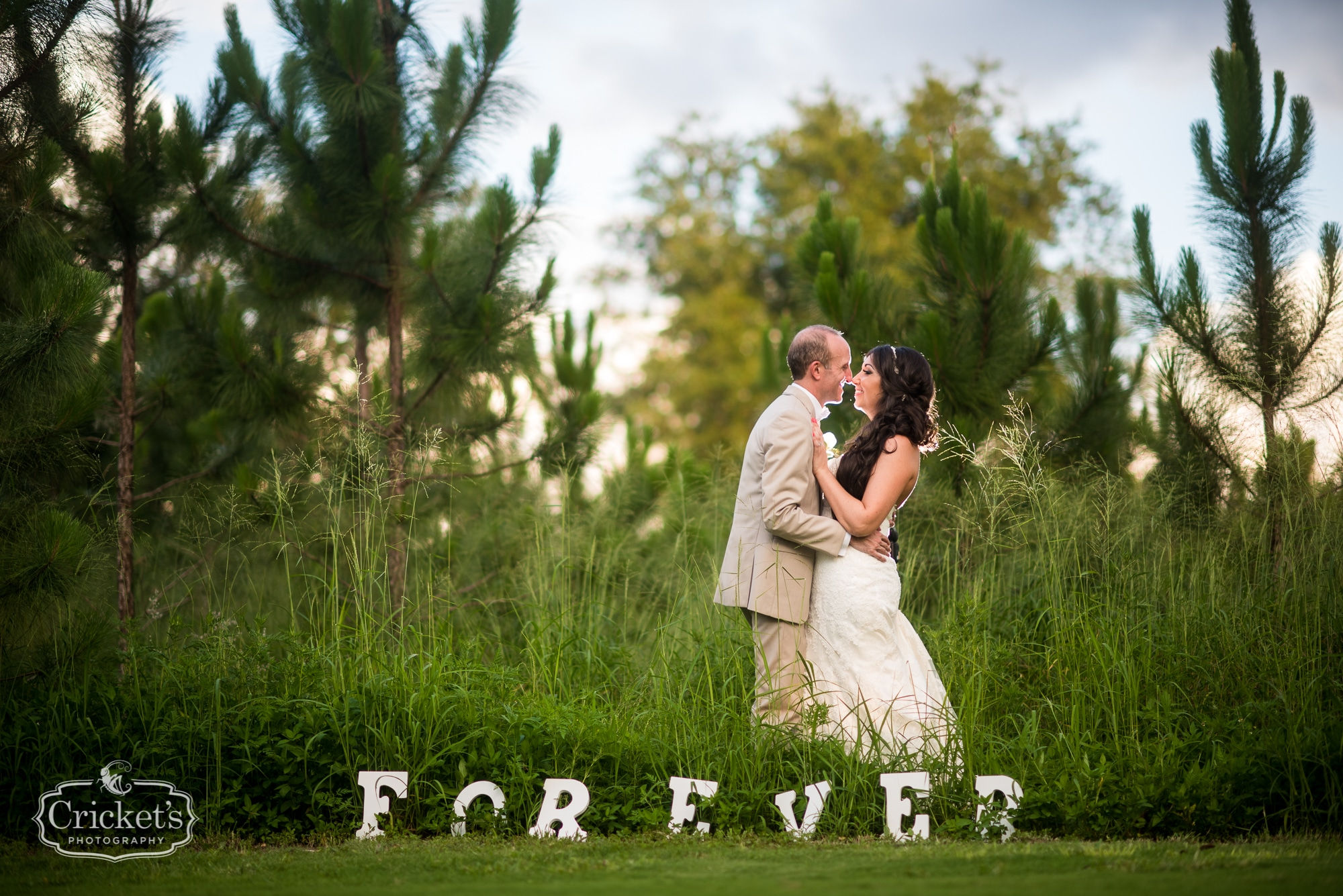 Bride and groom in tall grass with wooden letters that spell Forever
