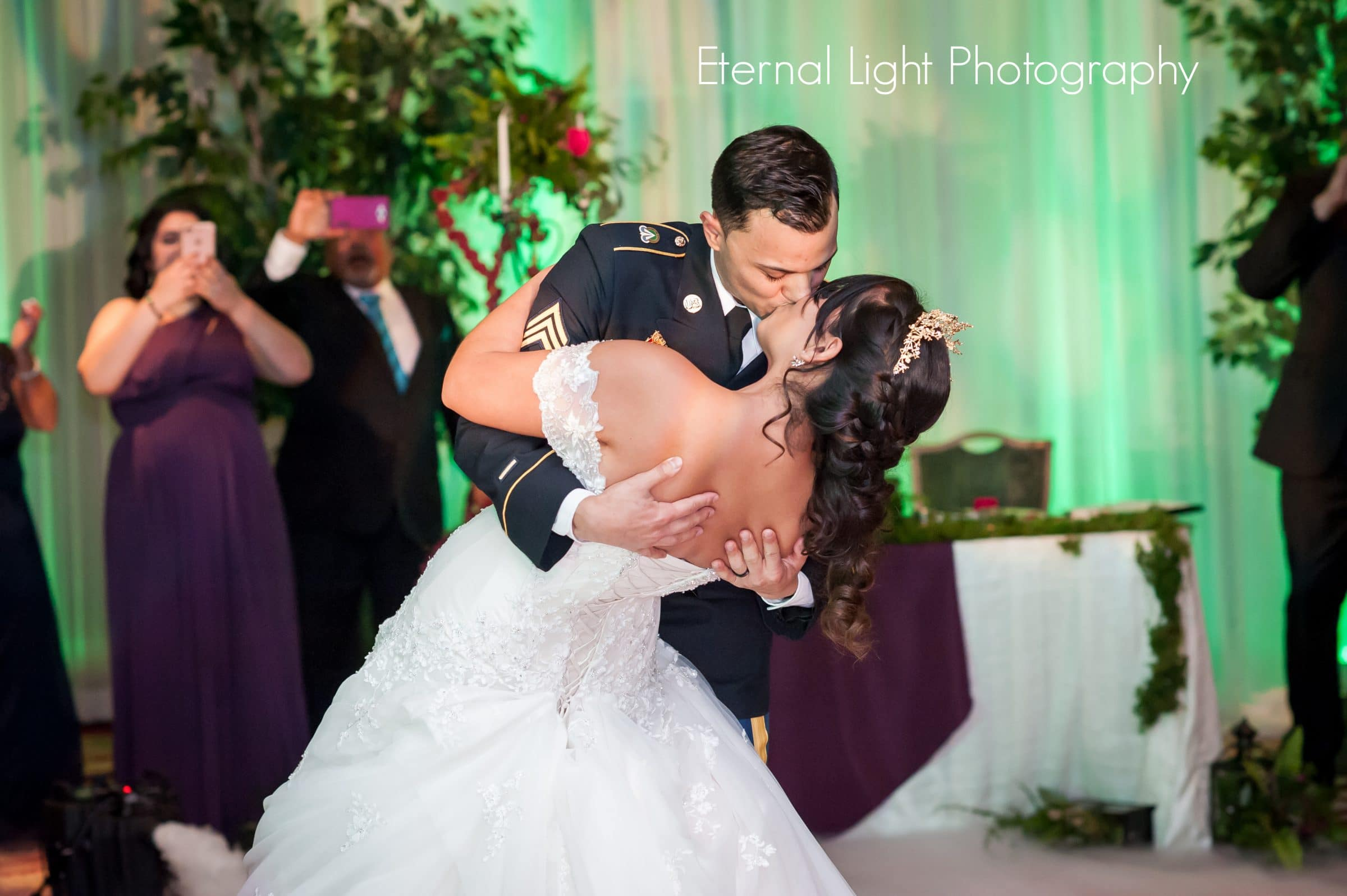 Military groom dipping and kissing bride during first dance