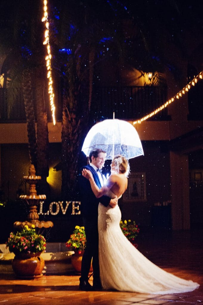 Bride and groom holding transparent umbrella in the Plaza de la Fontana