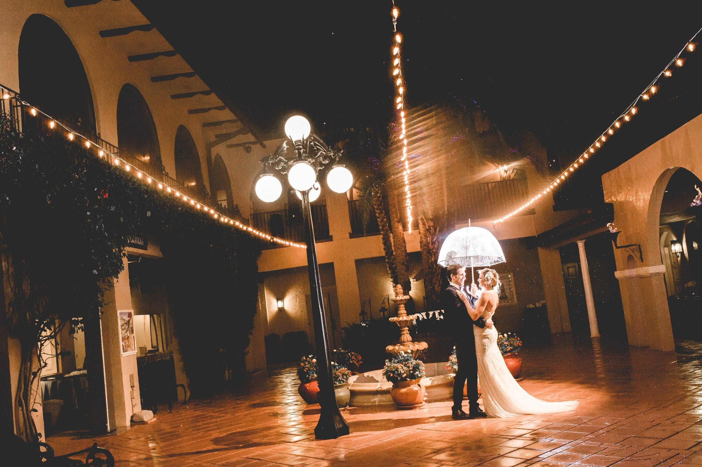 Bride and groom with umbrella in the rainy Plaza de las Palmas