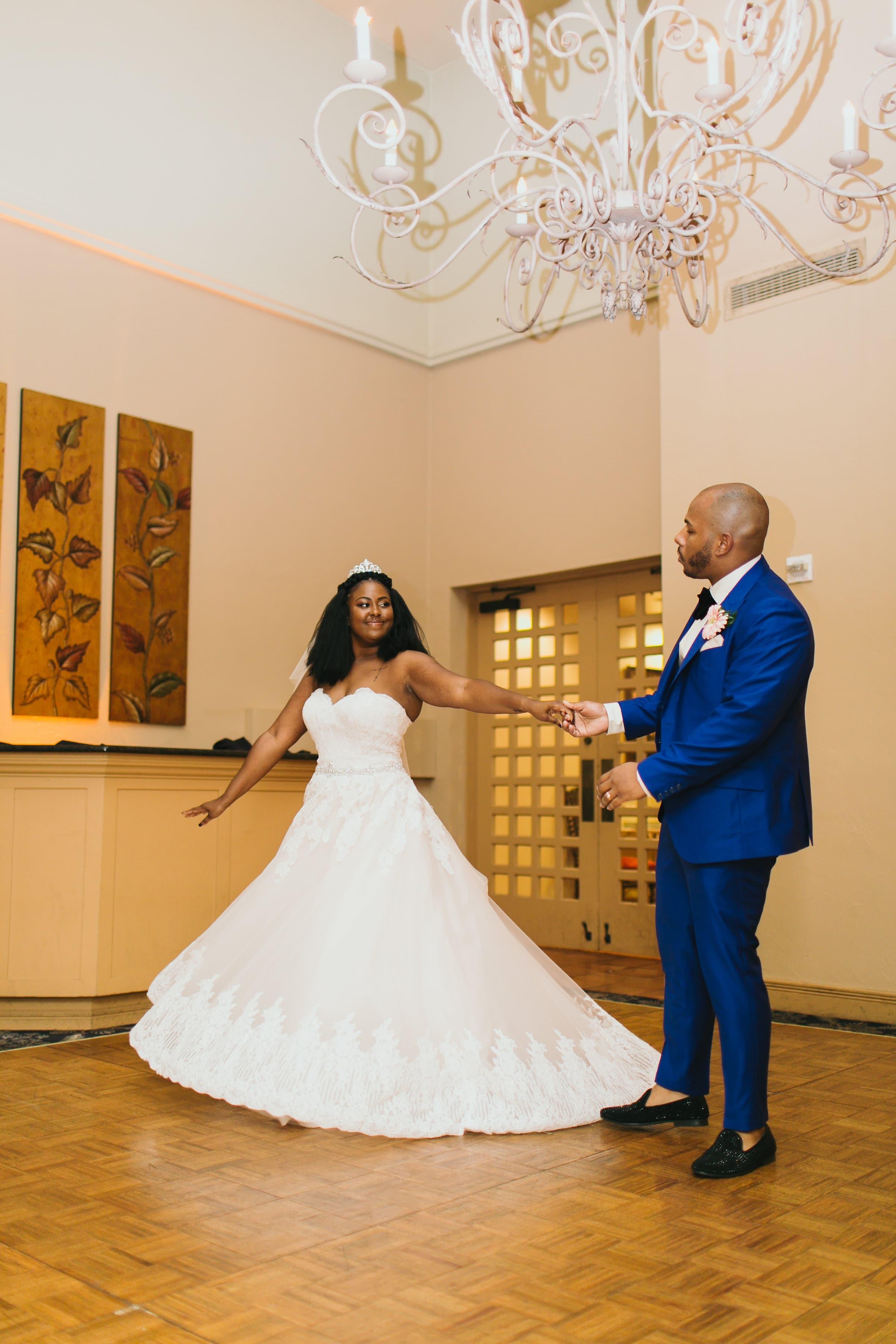 Groom twirling bride under chandelier at Legends Ballroom