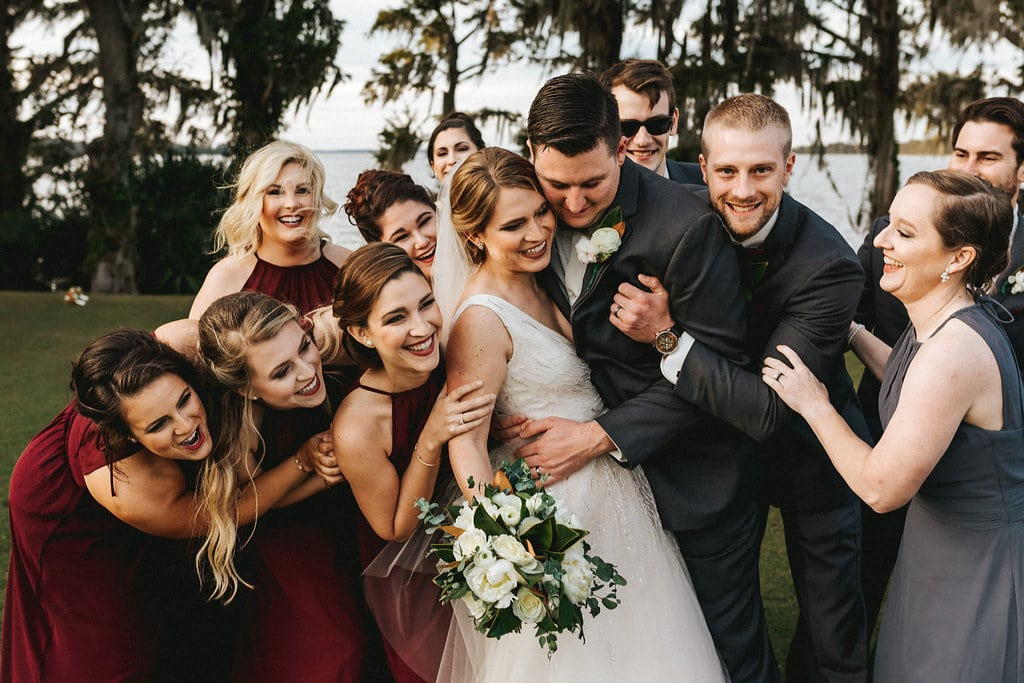 Wedding party crowded around hugging bride and groom