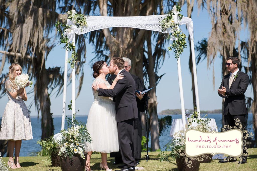 Bride and groom kissing under chuppah at Marina del Rey