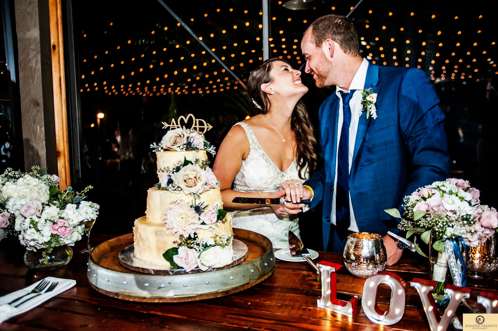 Bride and groom laughing at each other during cake cutting