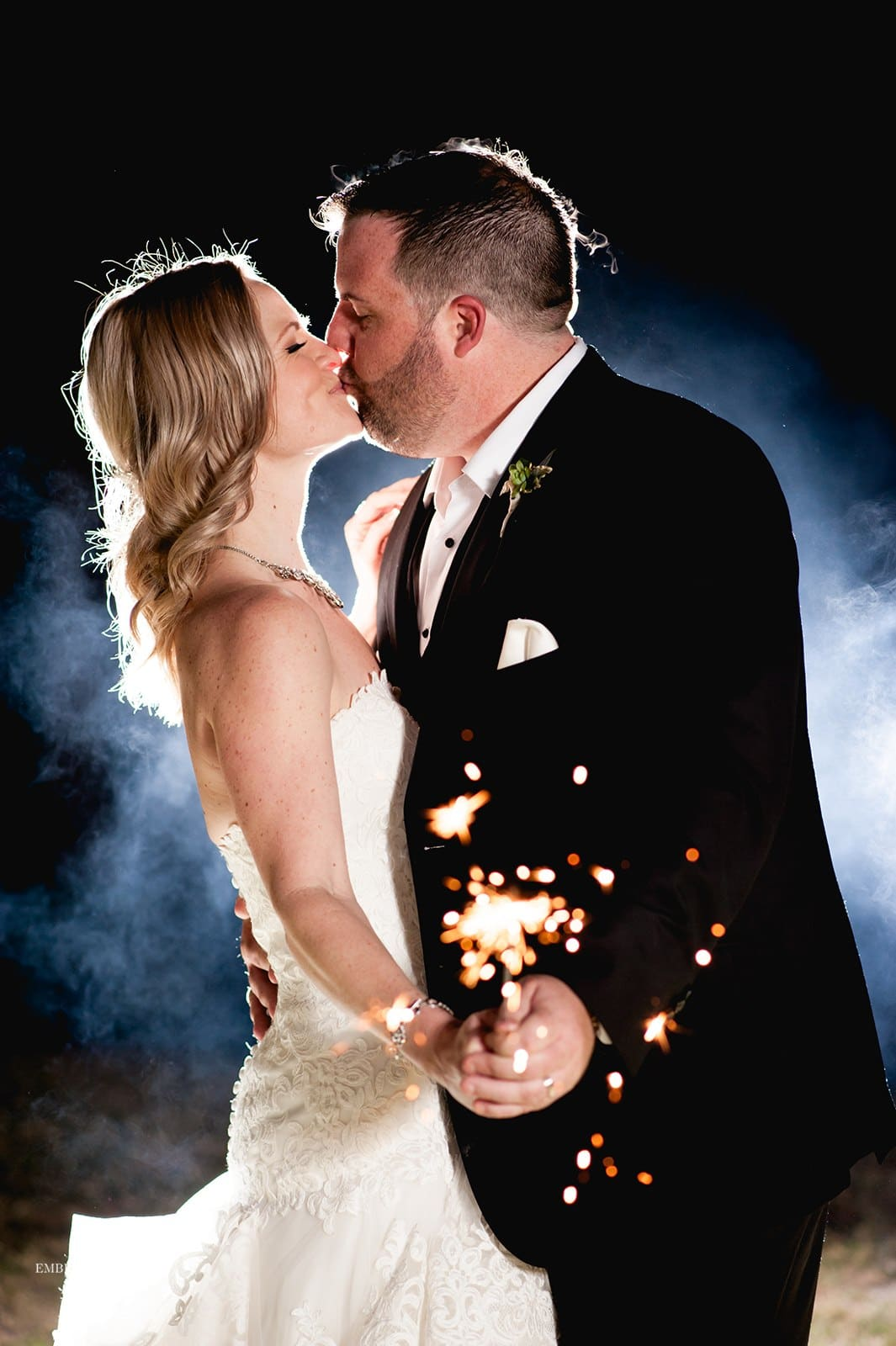 Bride and groom kissing holding shared sparkler