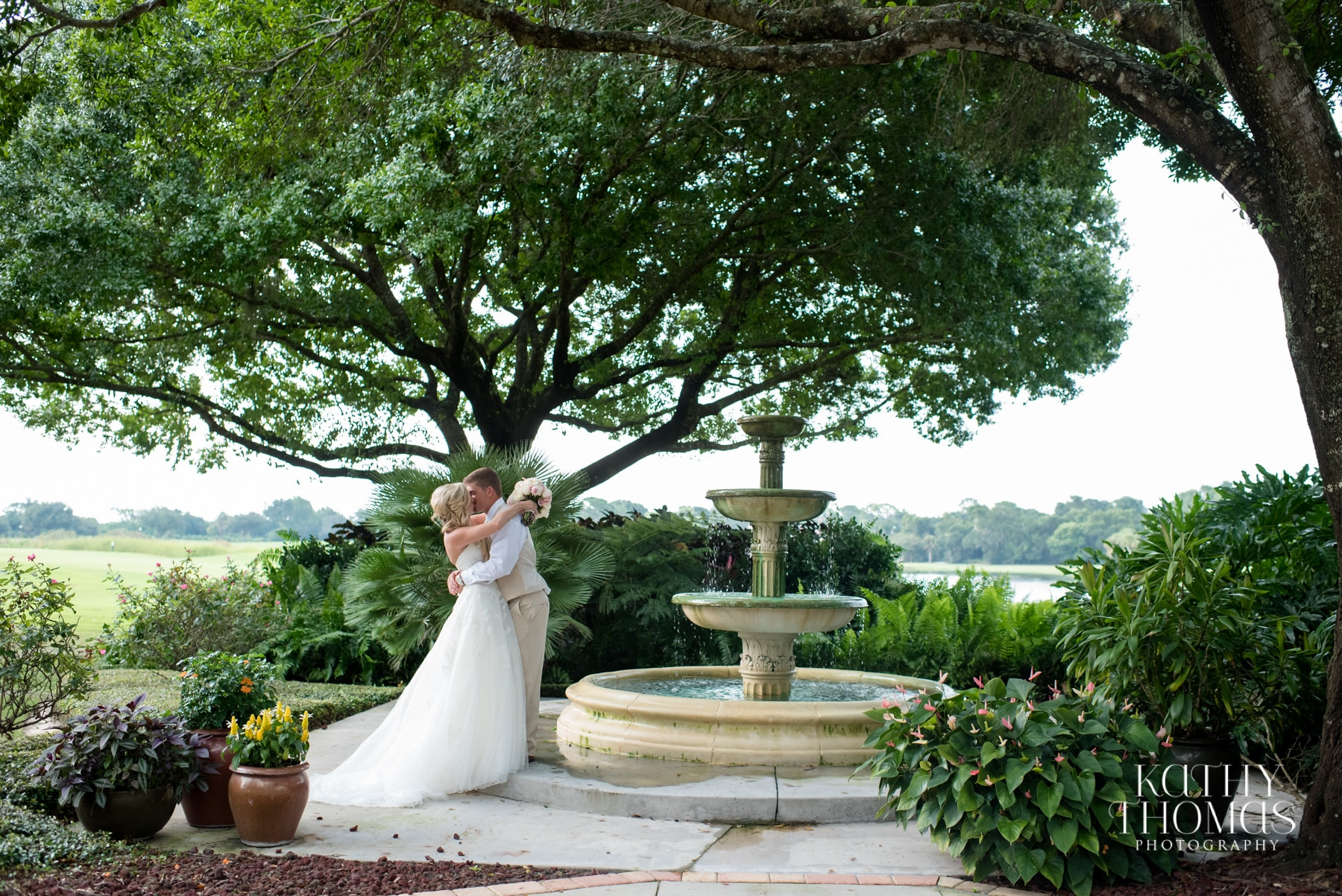 Bride and groom kissing beside beautiful rustic outdoor fountain