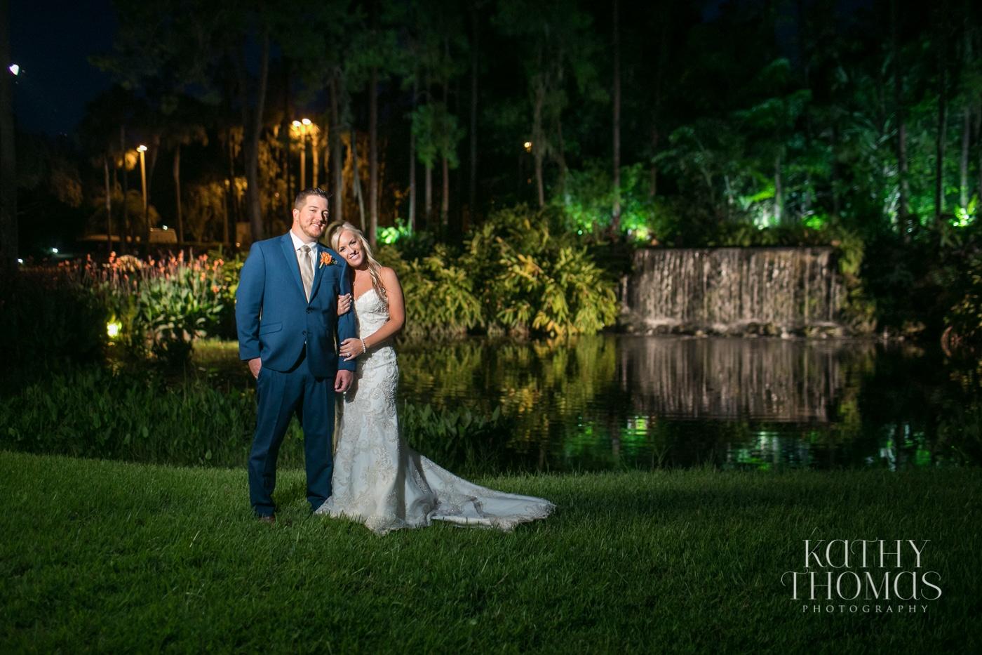 Bride and groom next to golf course waterfall at night
