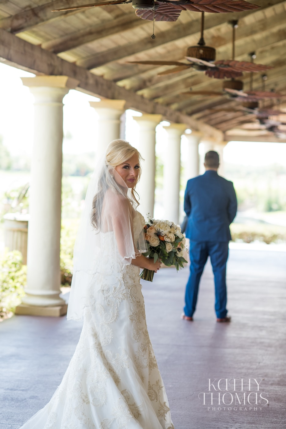 Groom with back turned under porch ceiling, bride glancing behind her as she approaches him