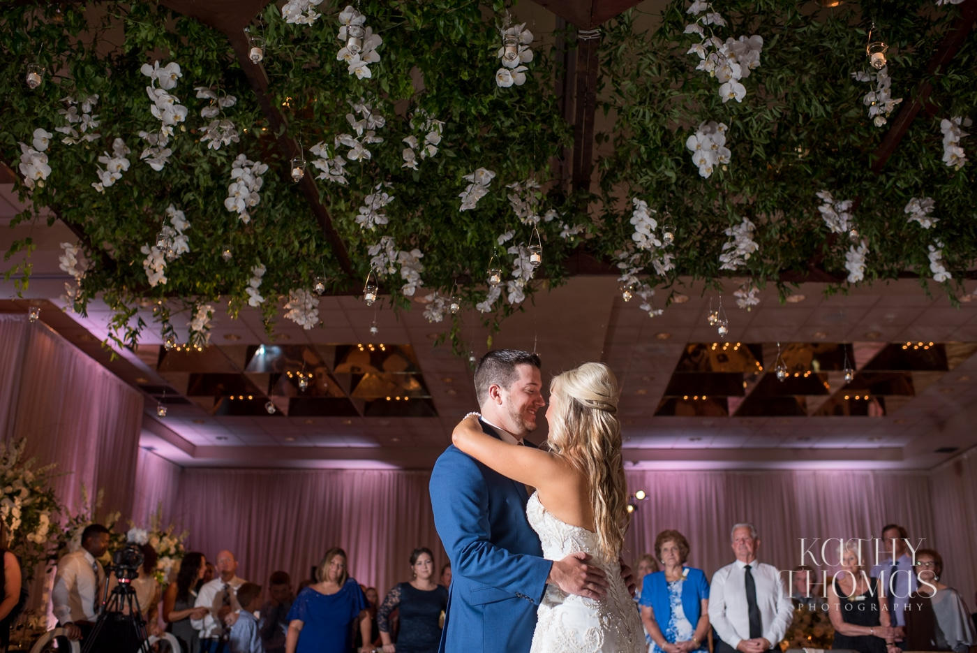 Bride and groom share first dance under ceiling hung with wisteria