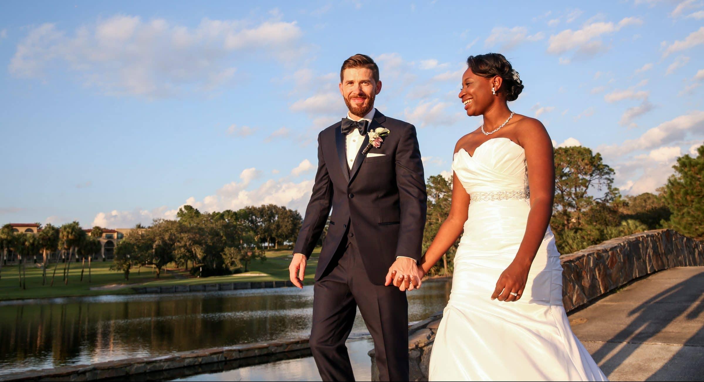 Bride and groom holding hands on stone bridge