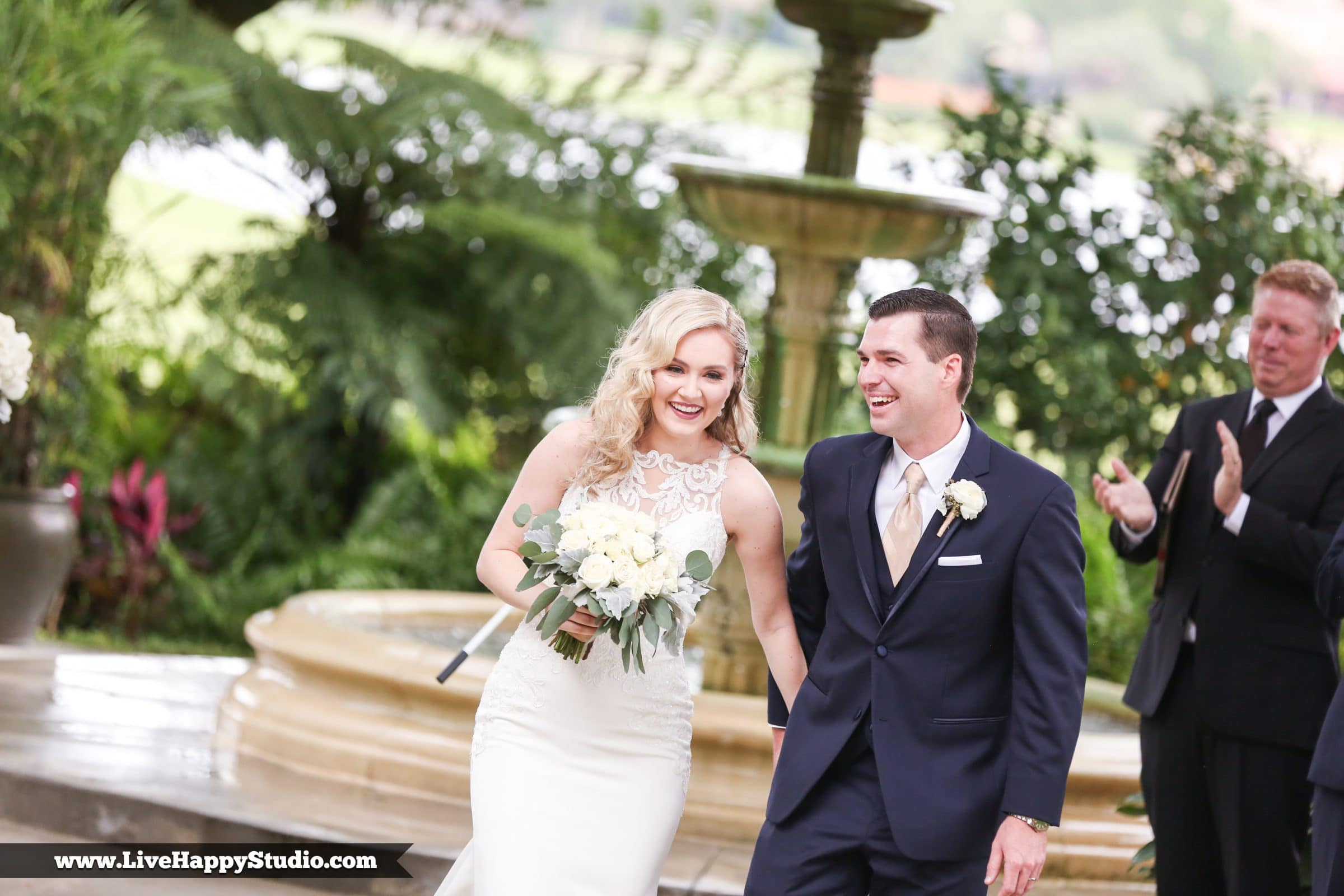 Bride and groom laughing in front of gorgeous rustic fountain in Legends Courtyard