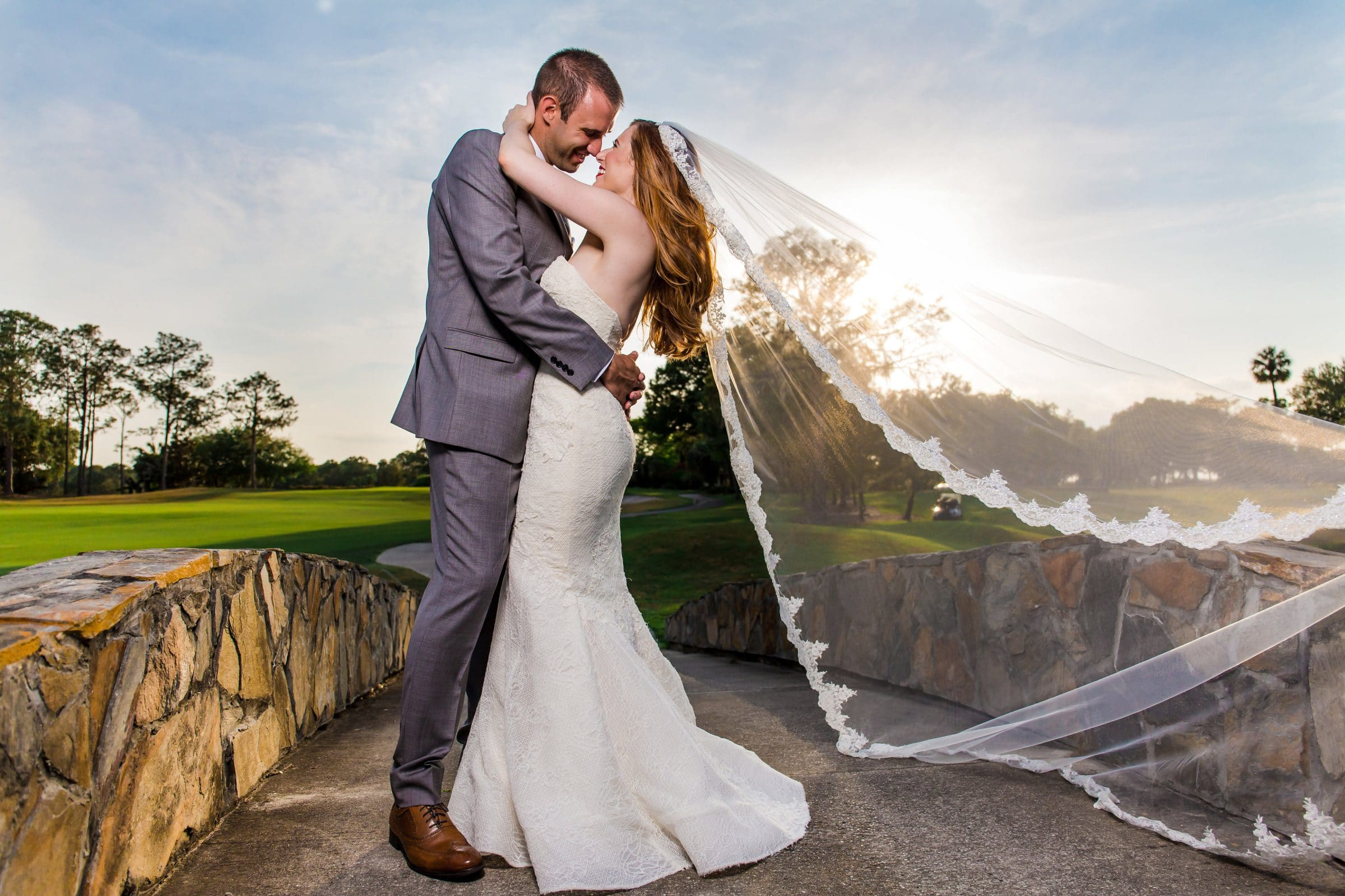 Gorgeous Portrait of Bride and groom holding each other on stone bridge at Mission Inn Resort
