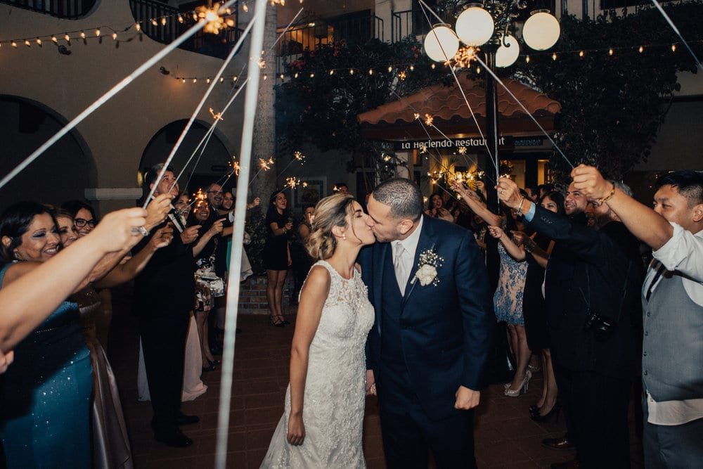 Bride and groom kissing during sparkler send off