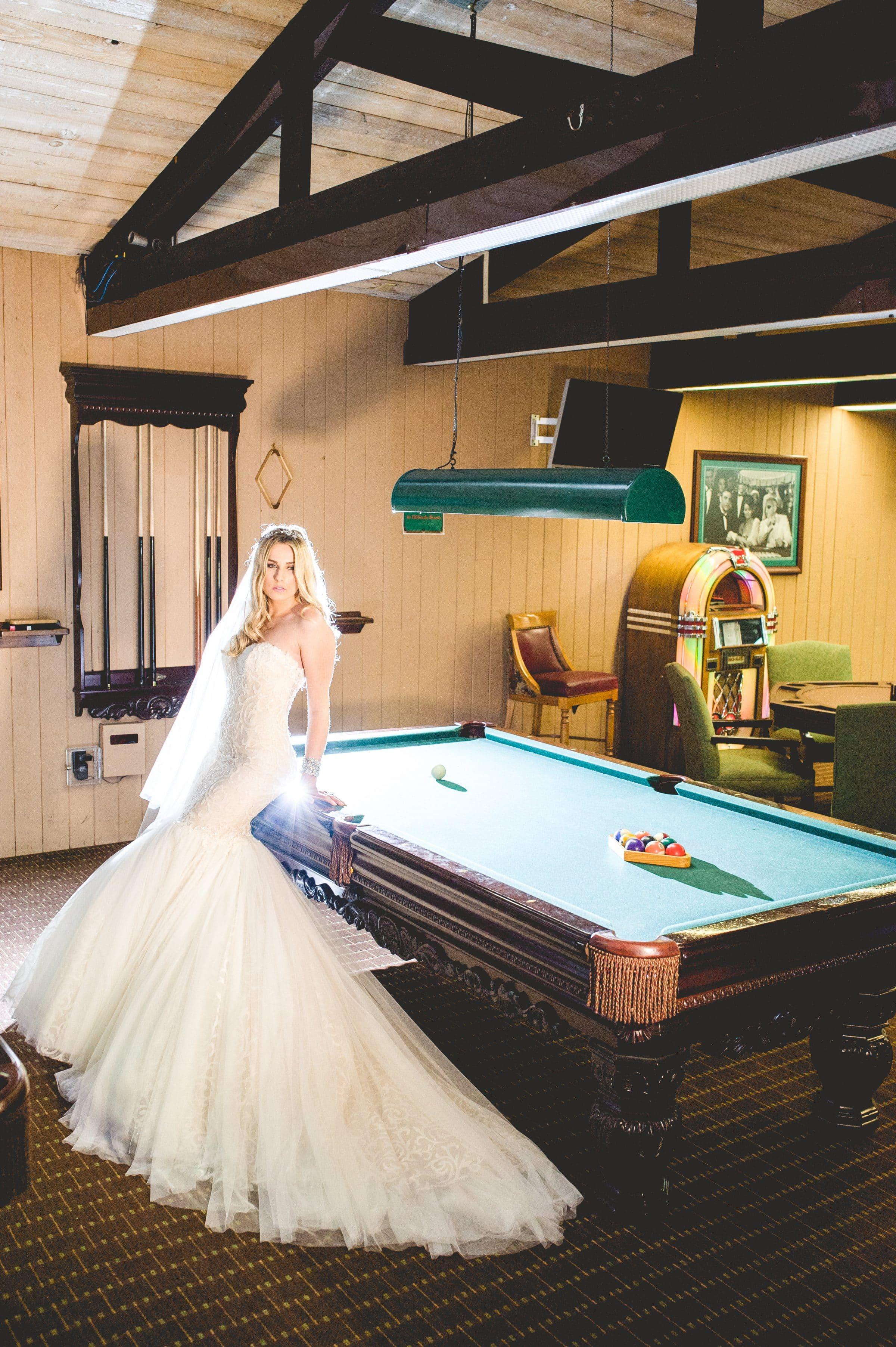 Bride wearing long mermaid gown in billiards room