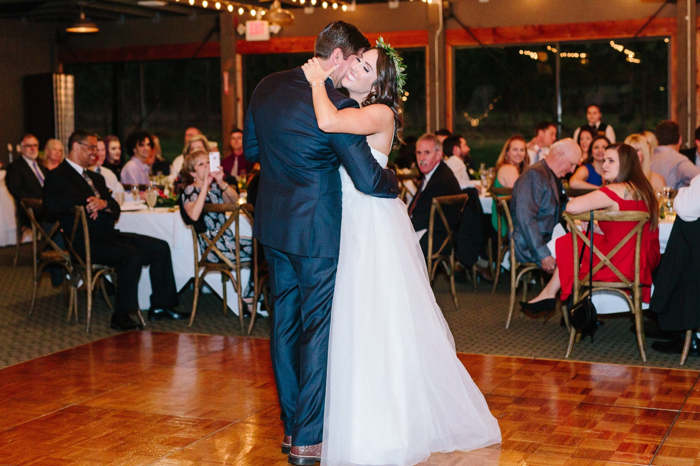 Boho chic bride with greenery headband shares first dance with groom