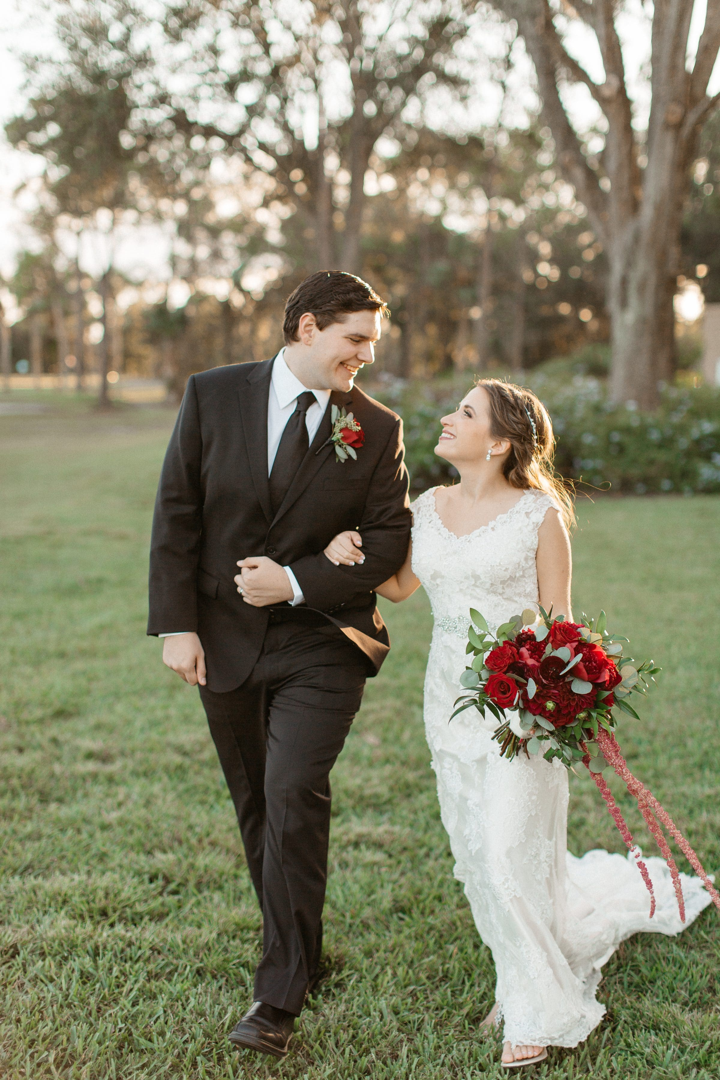 Bride and groom smiling at each other in field