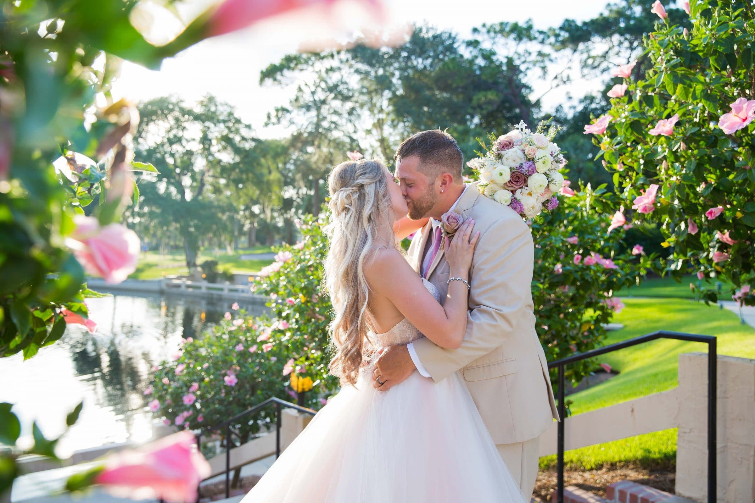 Kissing bride and groom on outdoor staircase flanked by pink hibiscus