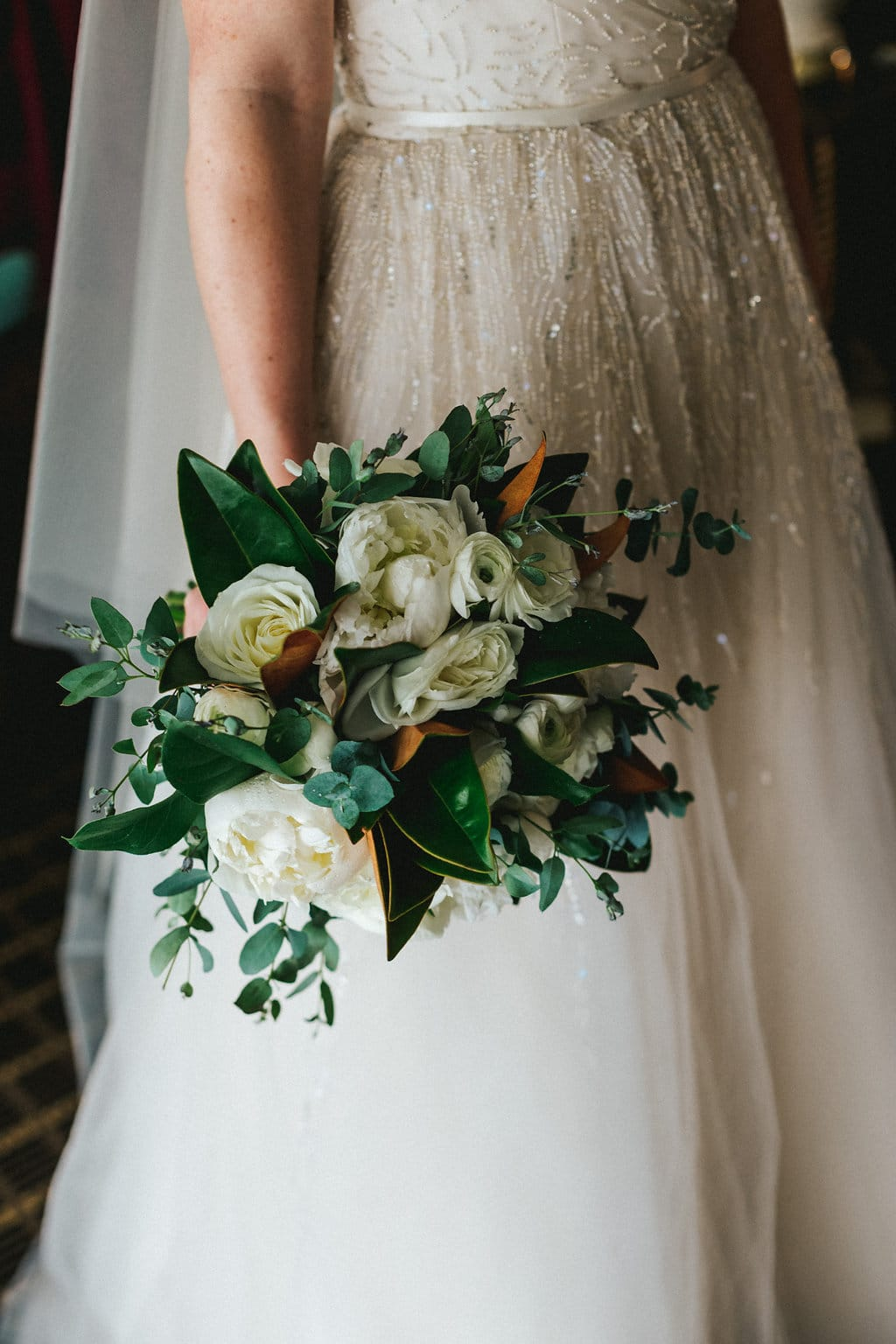 bride holding simple white and green bouquet
