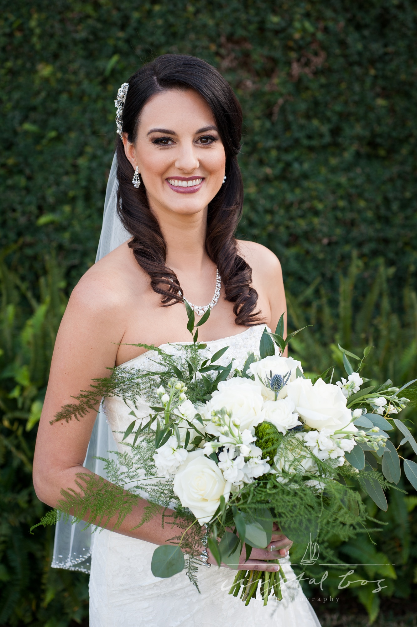 bride holding white and green bouquet with ferns