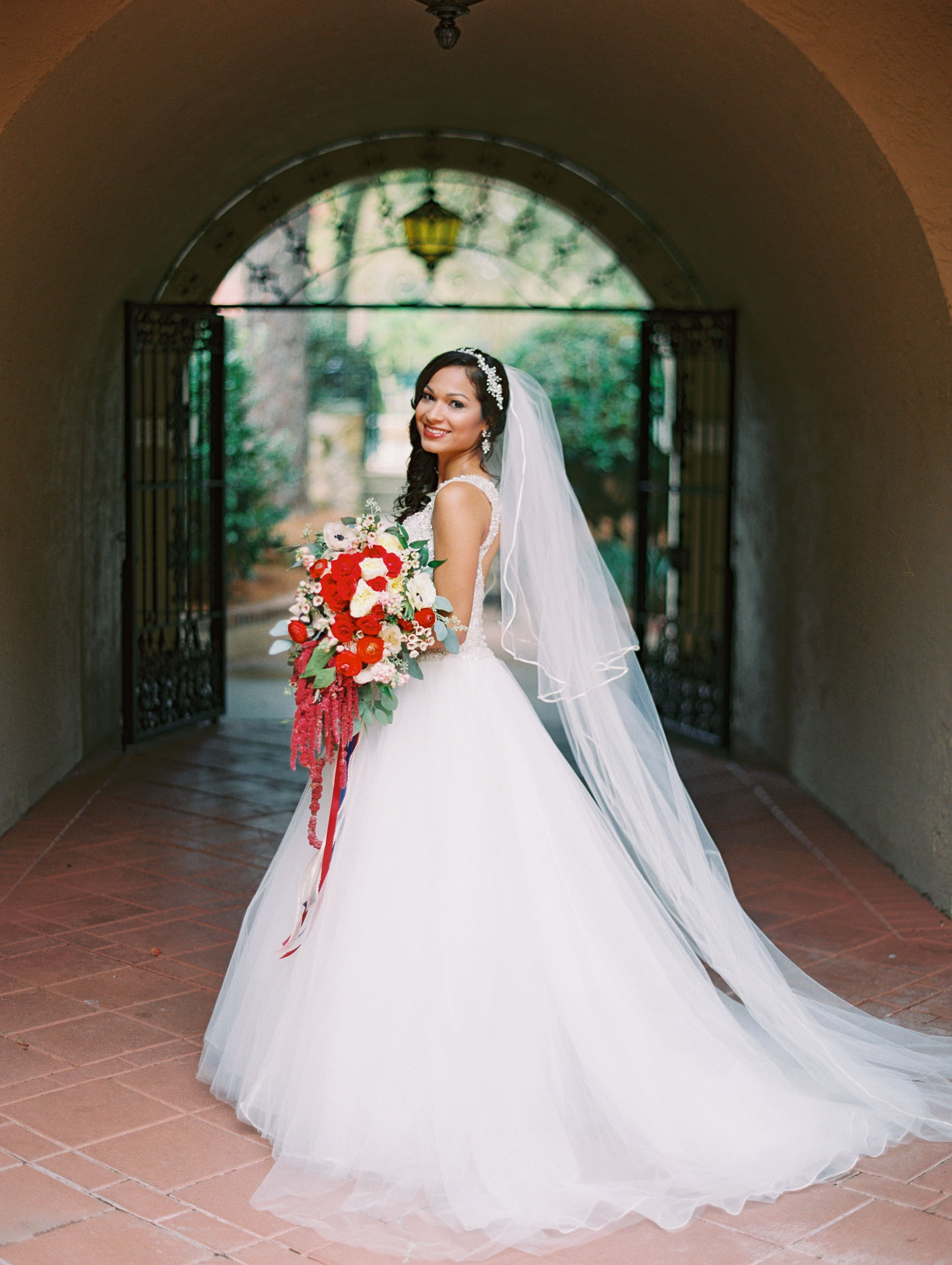 Lovely bride with cascading red bouquet in Spanish style architecture