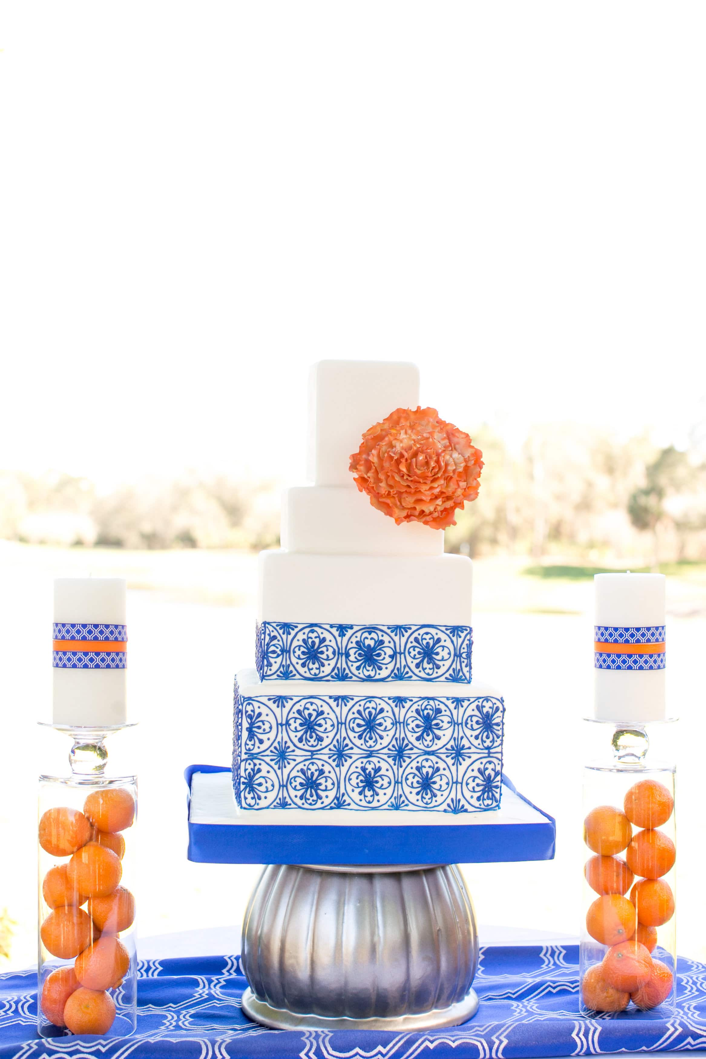 "square modern wedding cake with blue ""tile"" work and pops of orange"