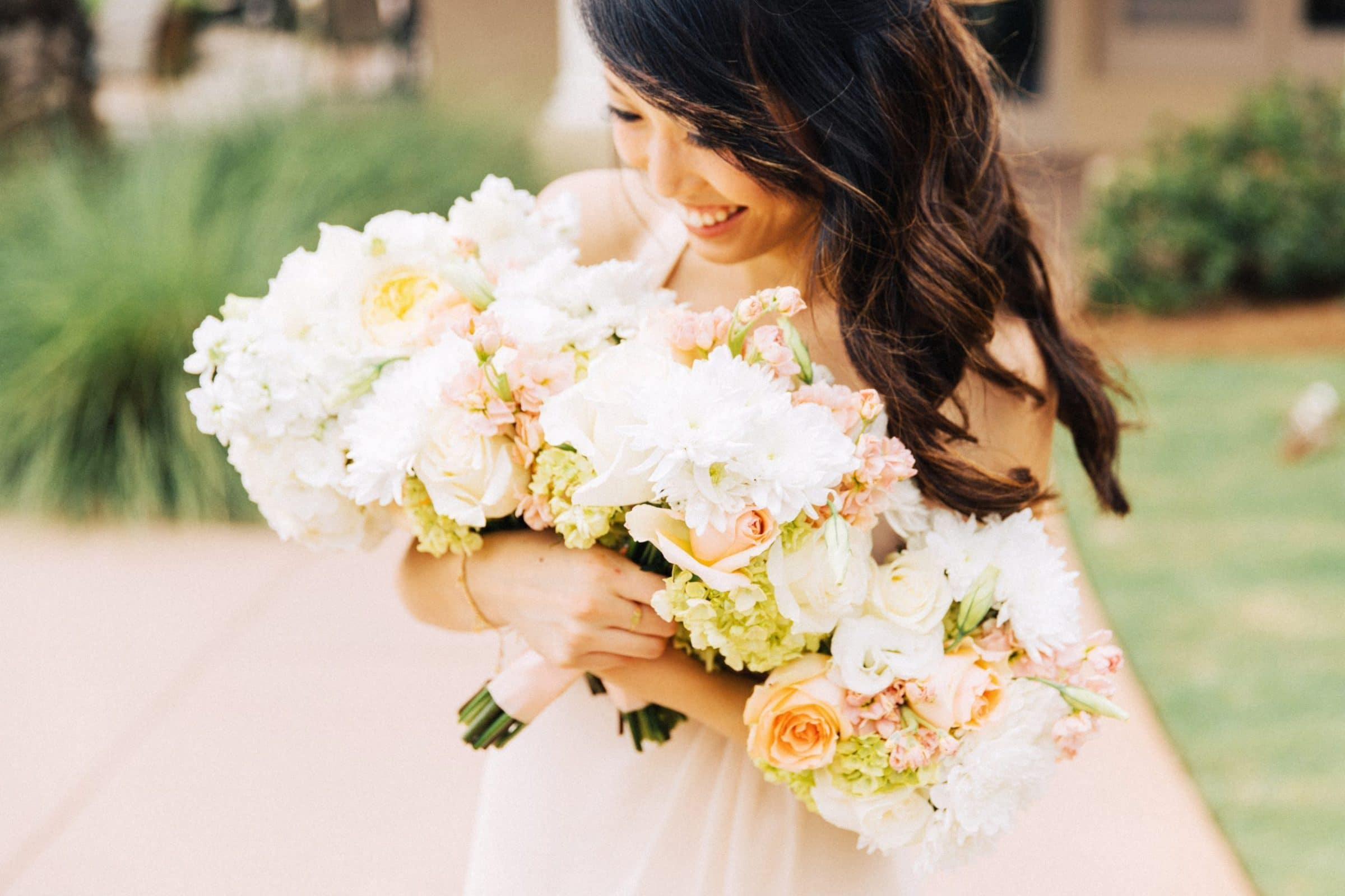 bride cradling multiple bouquets