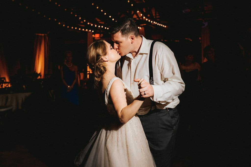 Bride and groom's first dance with dramatic market lighting at wedding reception
