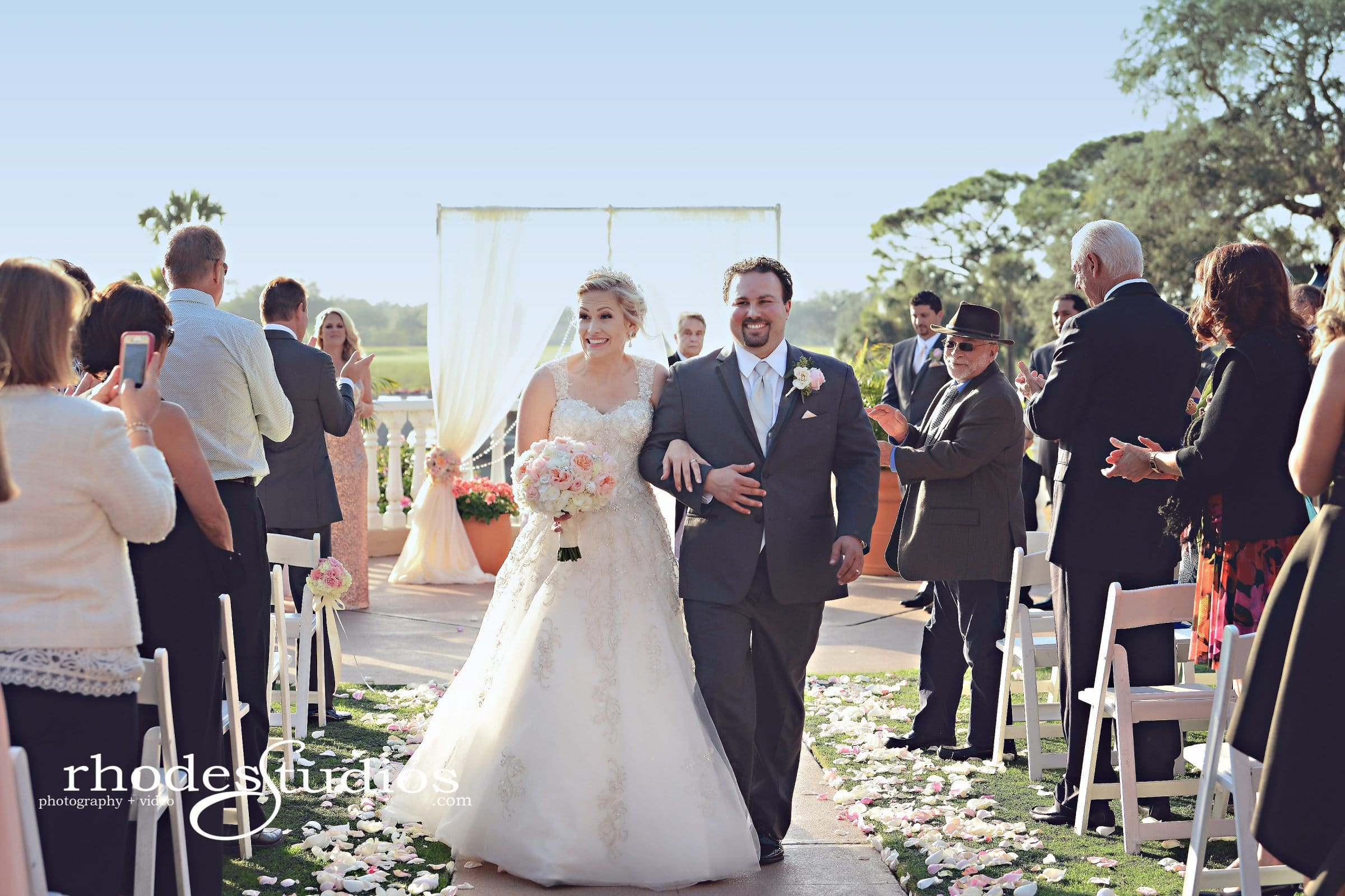 Smiling newlyweds walking down aisle lined with flower petals