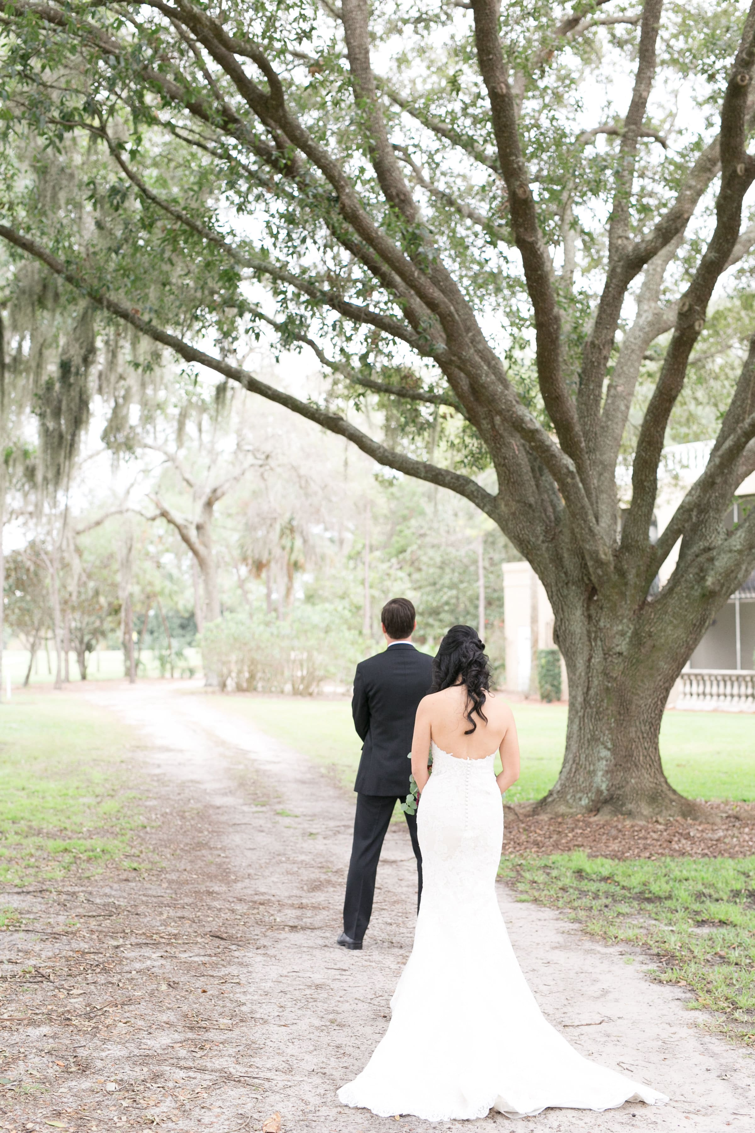 Groom turned around as bride approaches him under old oak tree