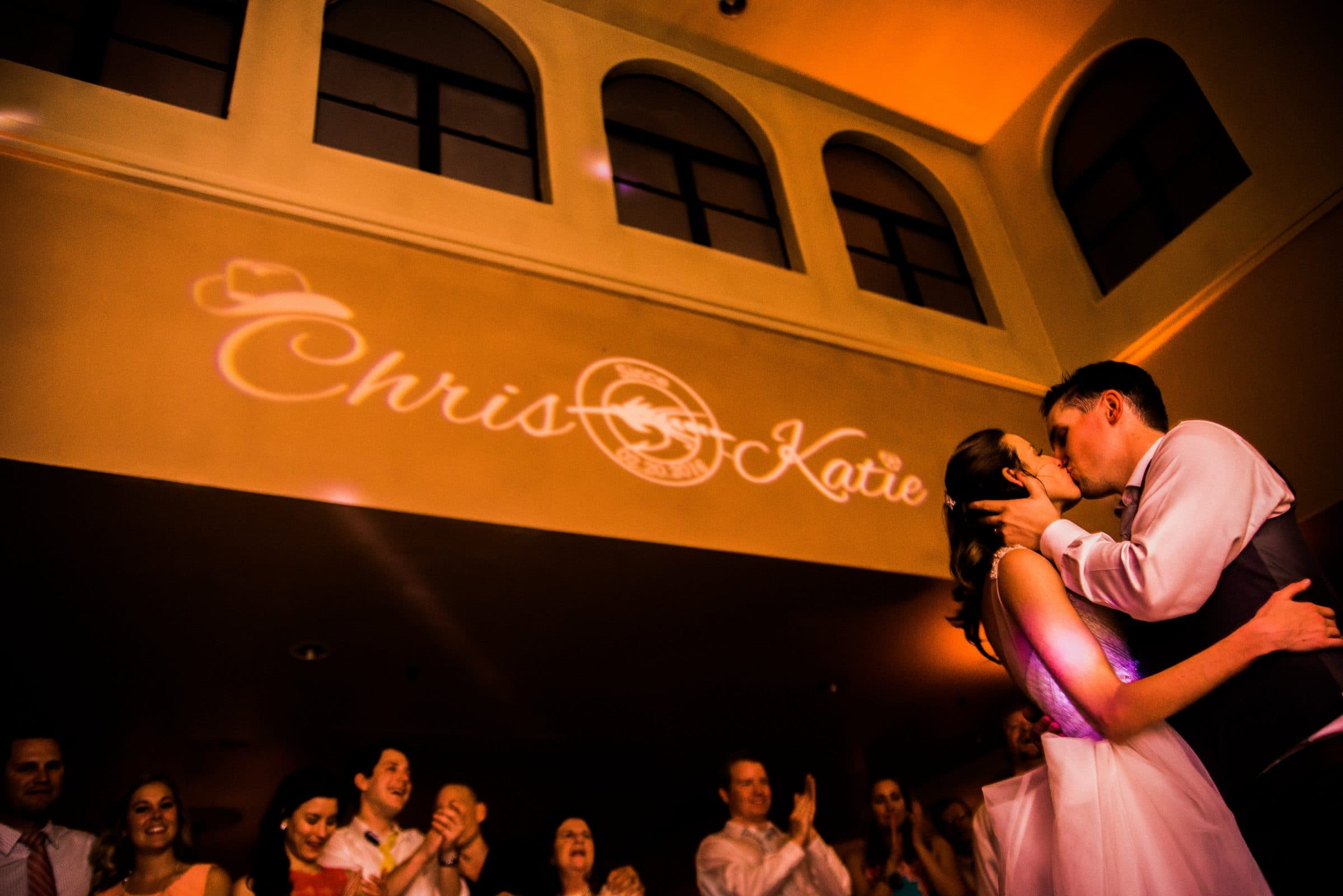 Chris and Katie kiss on dance floor underneath projected monogram of their names