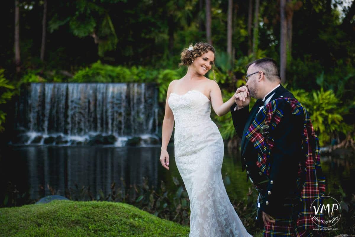 Portrait of Groom in Scottish wear kissing bride's hand