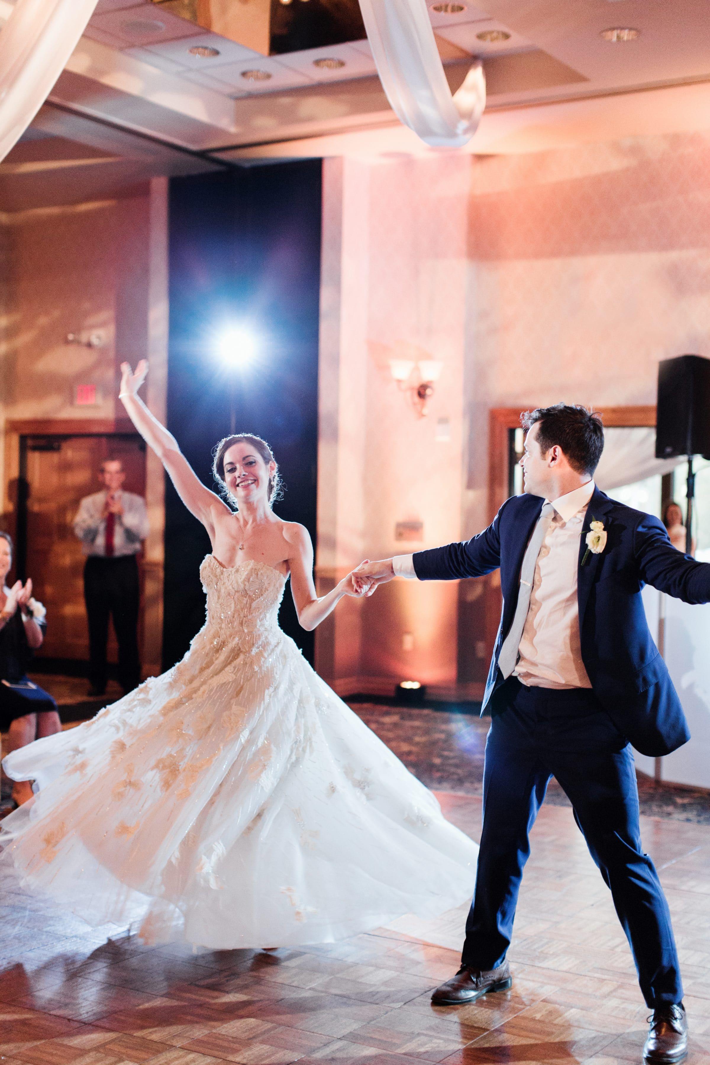 Groom twirling bride dramatically on dance floor at Mission Inn wedding reception