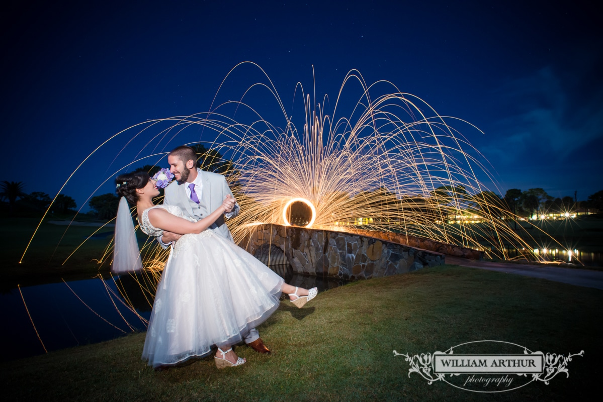 Groom dipping bride next to stone bridge with shower of sparks