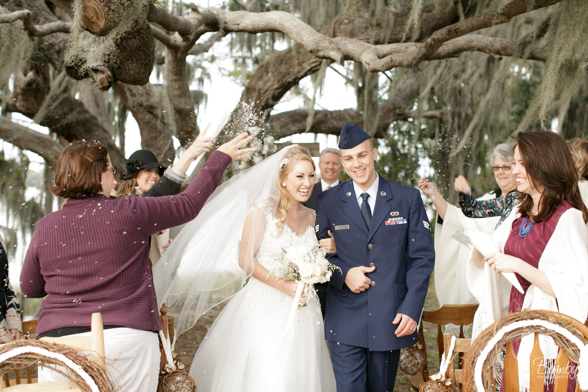 Wedding guests throwing confetti at bride and groom under sprawling oak tree
