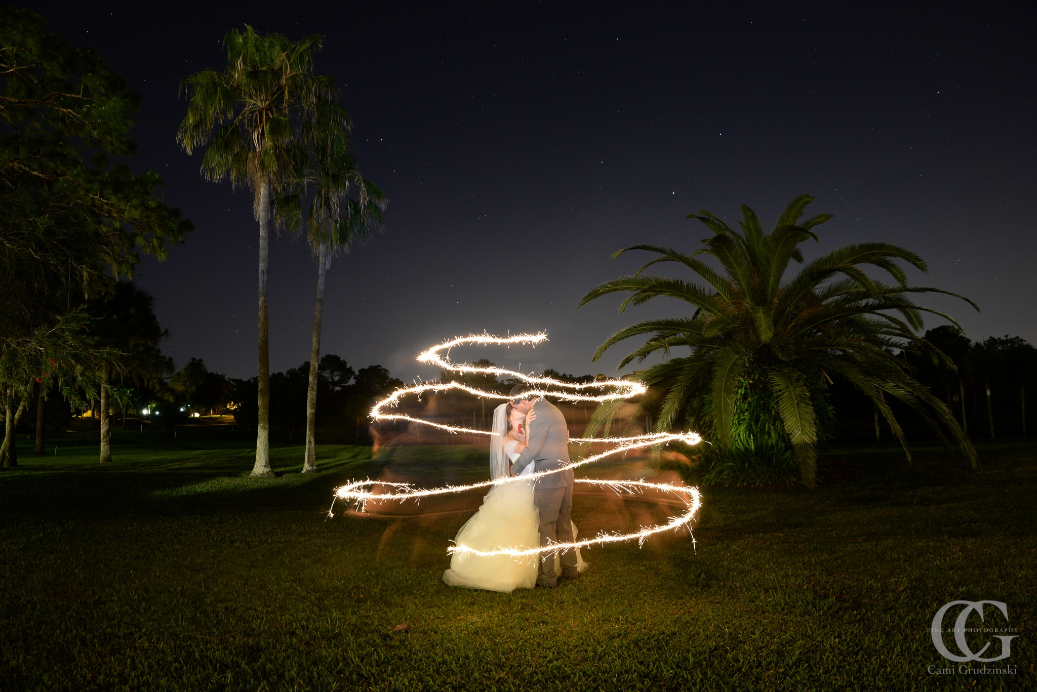 bride and groom kissing on golf course surrounded by a ribbon of light
