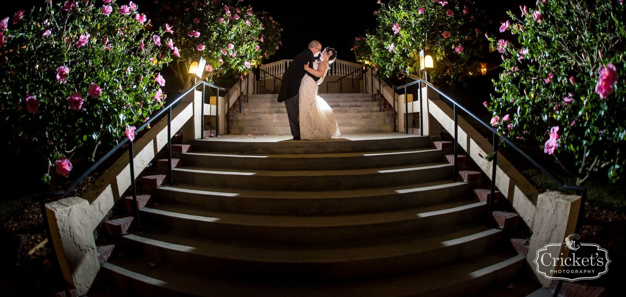 Bride and groom on outdoor staircase at night with dramatic lighting Questions to Ask Your Wedding Venue