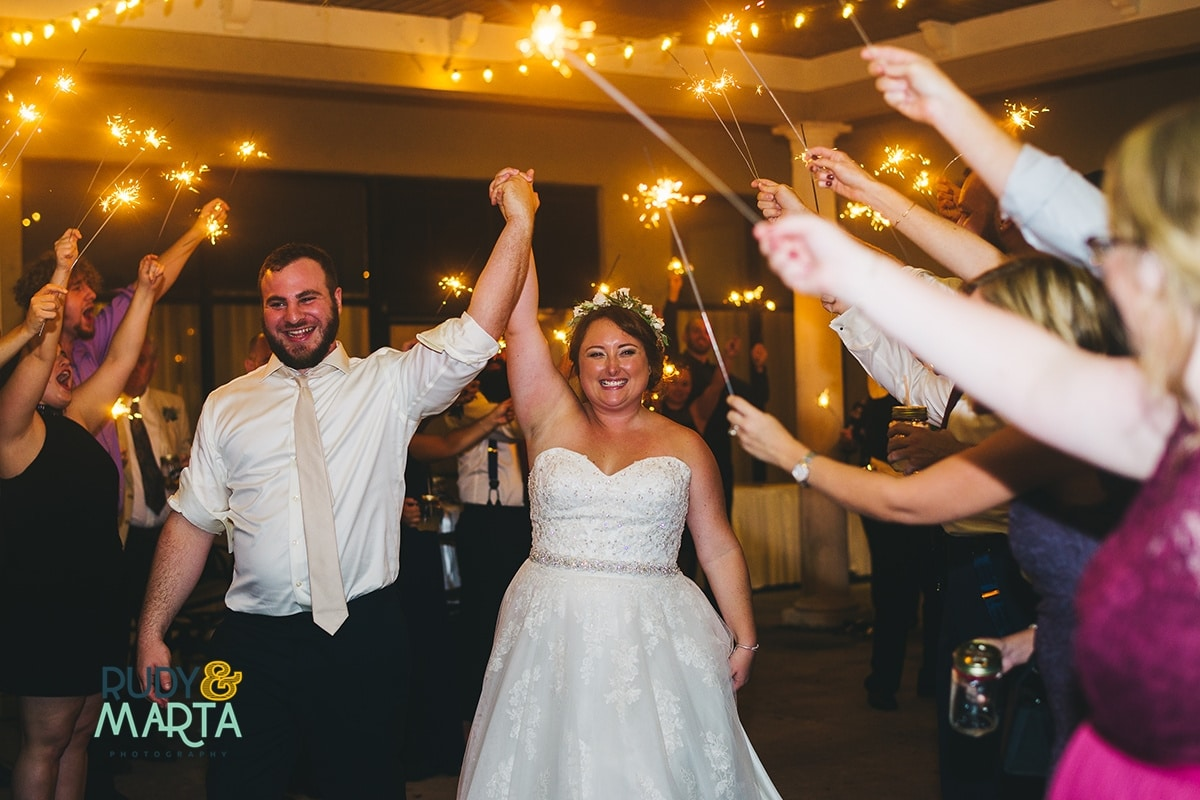Bride and groom raising held hands during sparkler sendoff